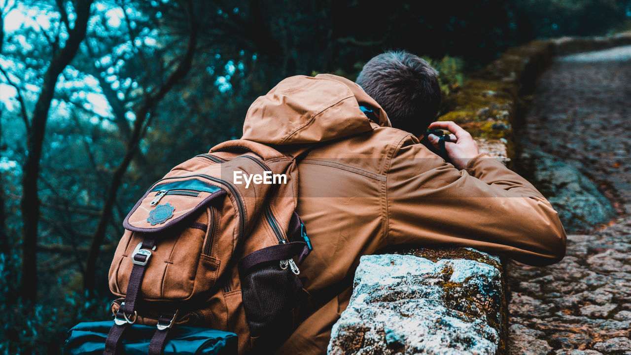 Rear View Of Man Carrying Backpack At Forest