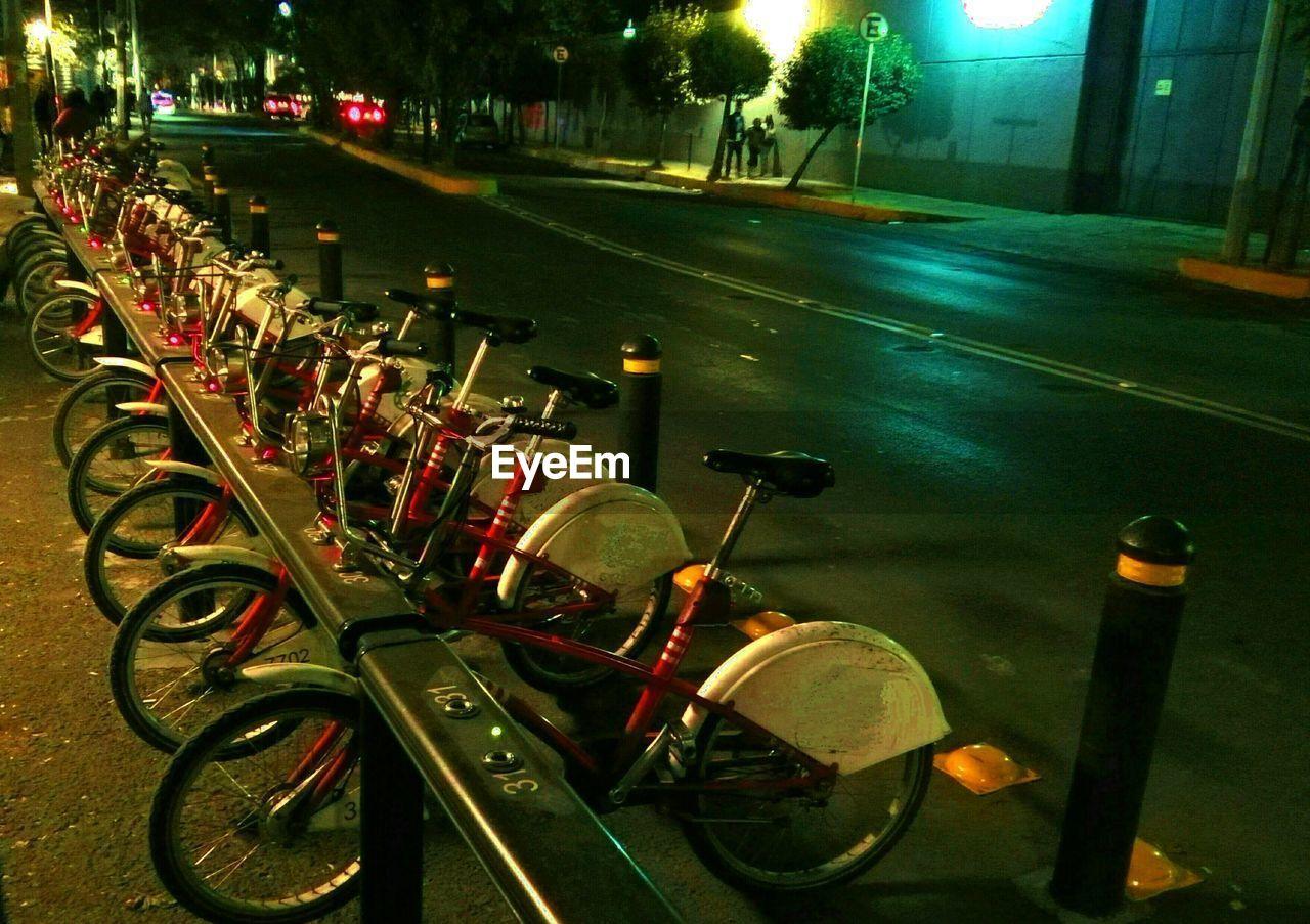 transportation, land vehicle, night, road, illuminated, outdoors, bicycle, stationary, no people, tree, city