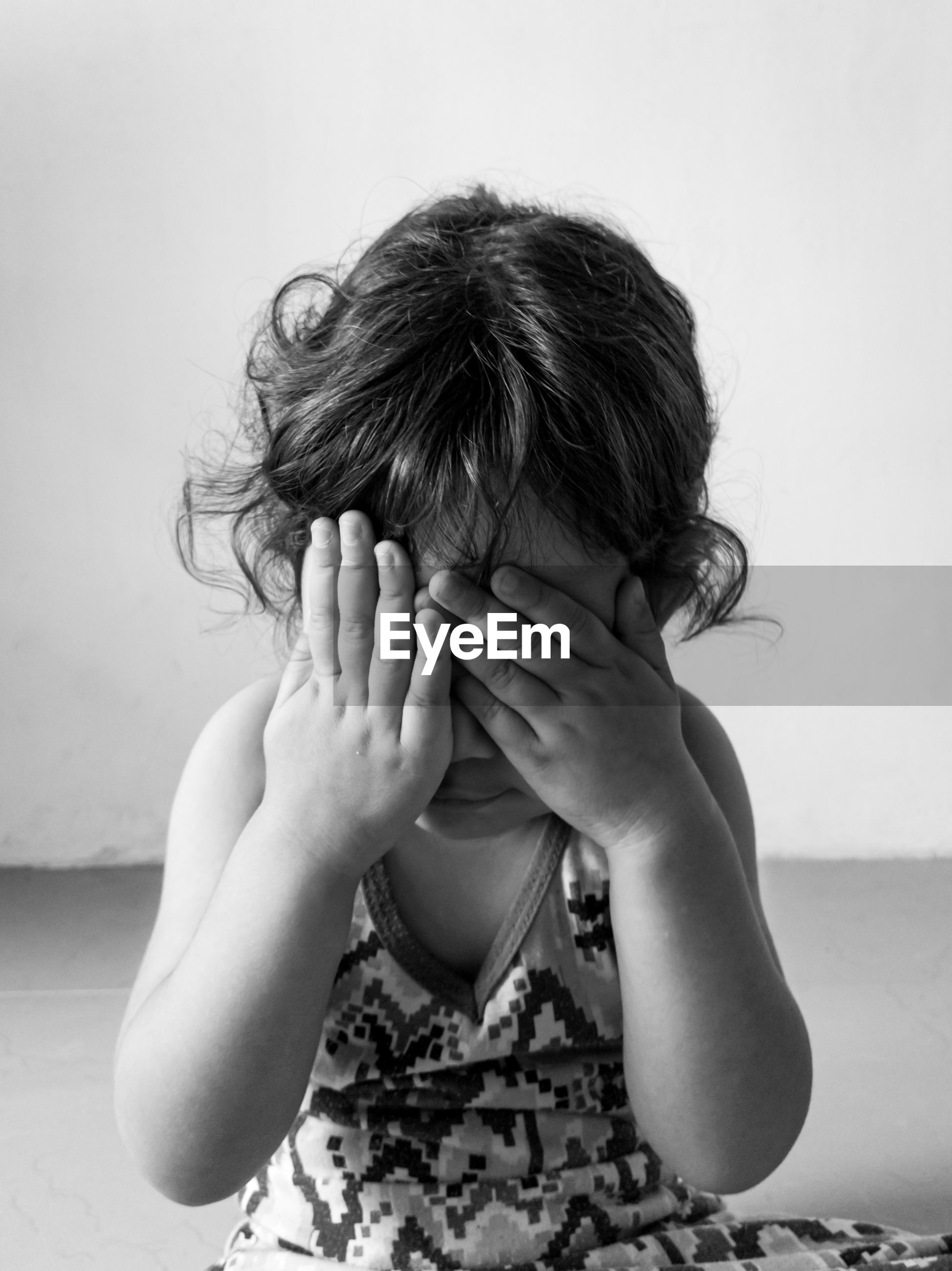 Portrait of little girl covering face with hand