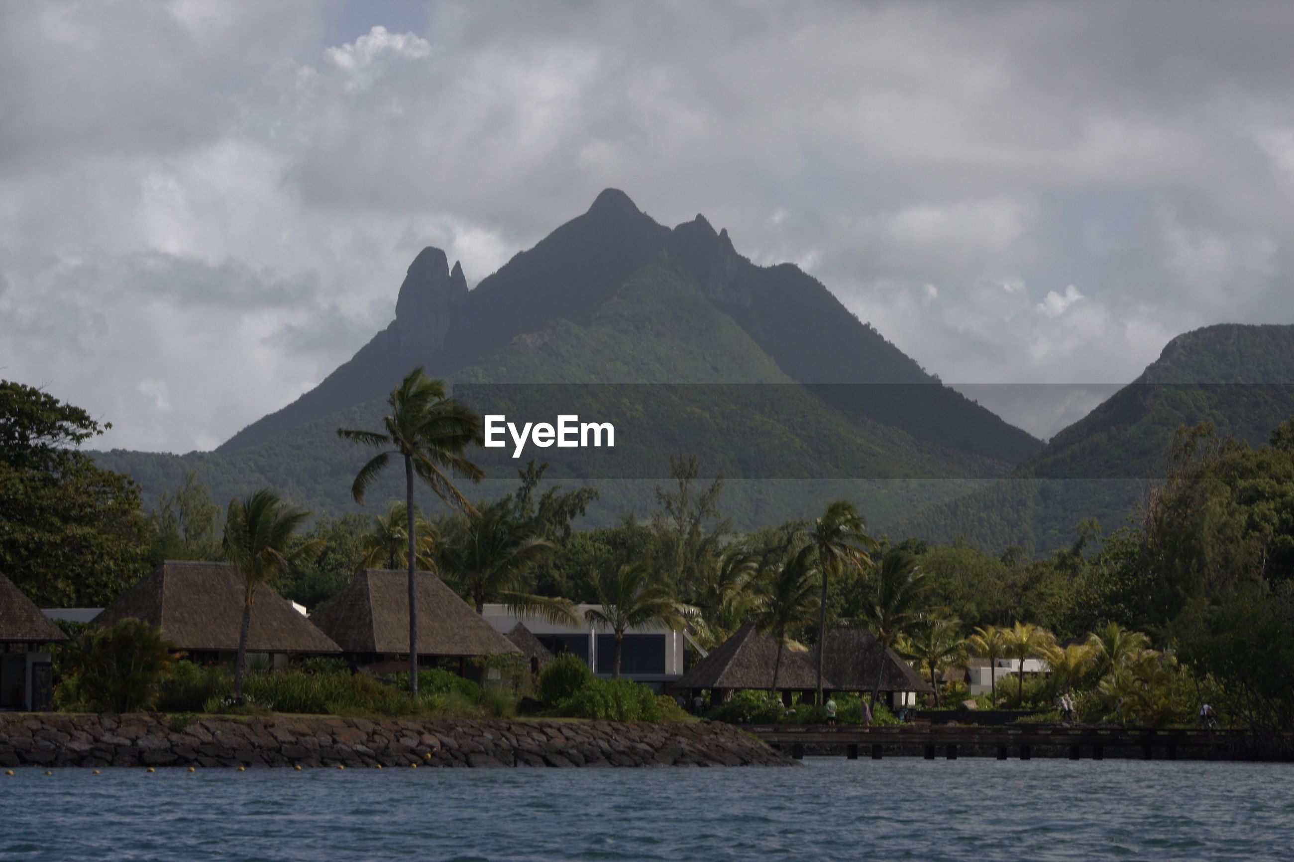 Scenic view of sea by buildings and mountains against sky