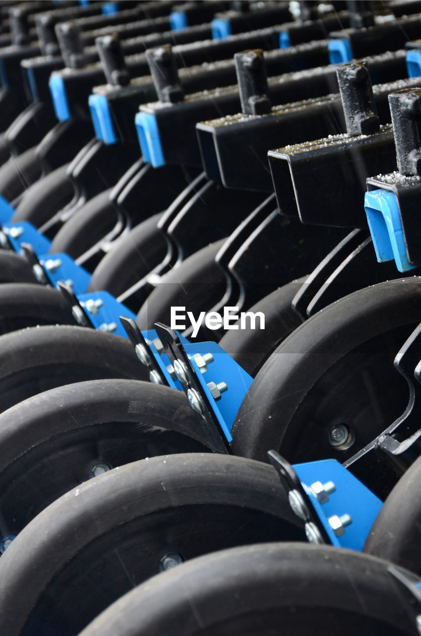 full frame, no people, in a row, close-up, backgrounds, blue, sport, transportation, seat, wheel, day, indoors, metal, black color, selective focus, large group of objects, mode of transportation, chair, absence, repetition, tire, weight training