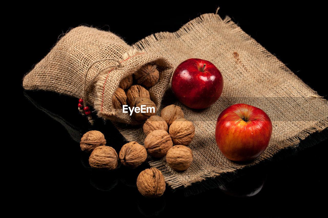 fruit, food, food and drink, healthy eating, wellbeing, freshness, still life, black background, apple - fruit, studio shot, indoors, no people, close-up, sack, nut - food, nut, cut out, burlap, red, walnut, jute