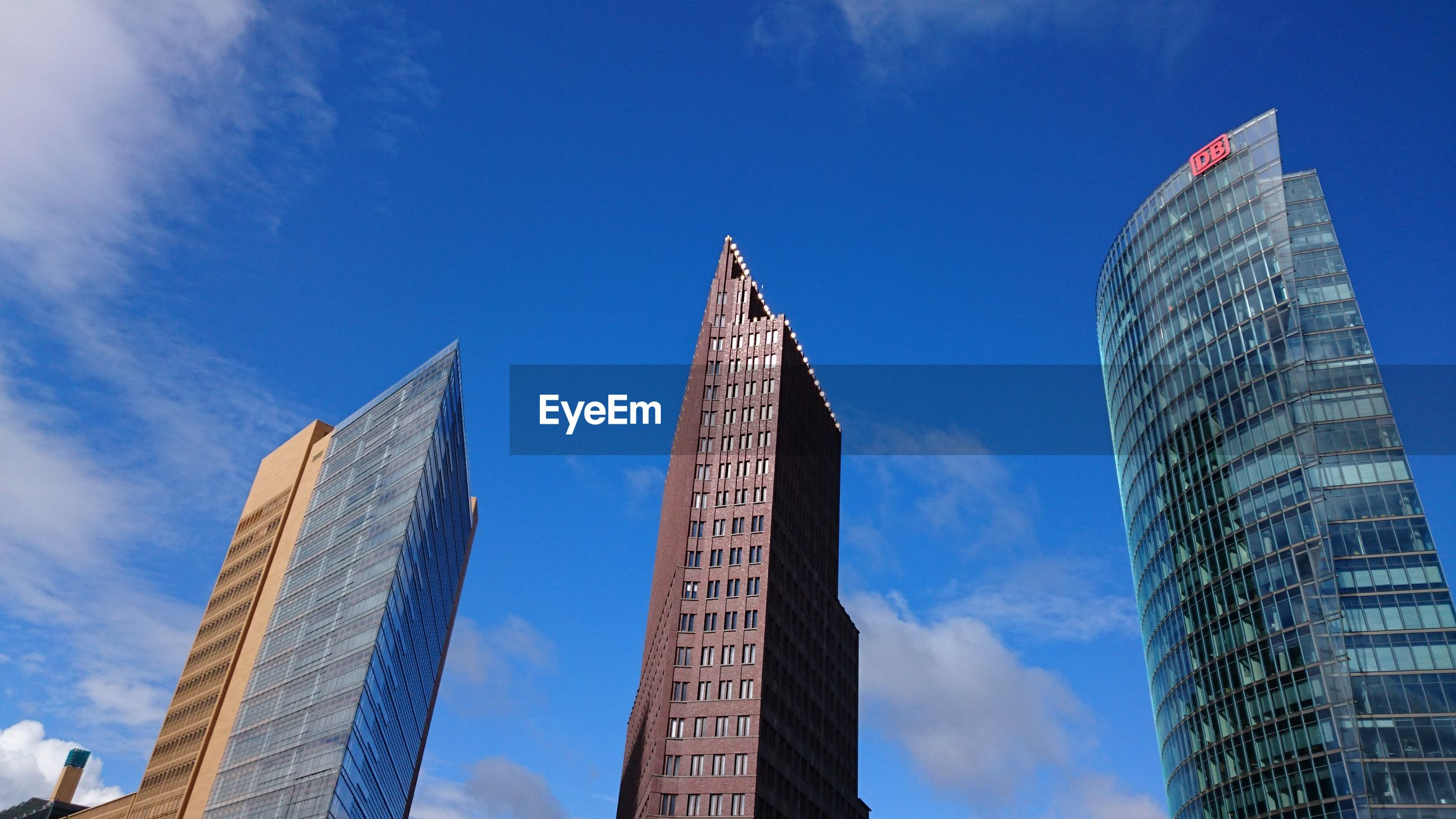 architecture, building exterior, built structure, tall - high, skyscraper, low angle view, tower, city, modern, office building, sky, capital cities, blue, famous place, travel destinations, tall, cloud - sky, day, city life, outdoors, financial district, tourism, cloud, no people, development