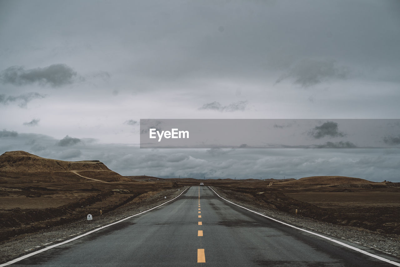Empty Road Amidst Landscape Against Sky