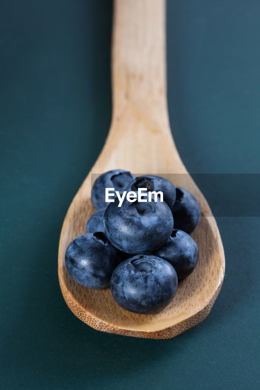 food and drink, healthy eating, food, freshness, wellbeing, close-up, still life, kitchen utensil, spoon, eating utensil, no people, indoors, studio shot, table, blueberry, fruit, berry fruit, focus on foreground, wood - material, black color, black background, wooden spoon, blue background