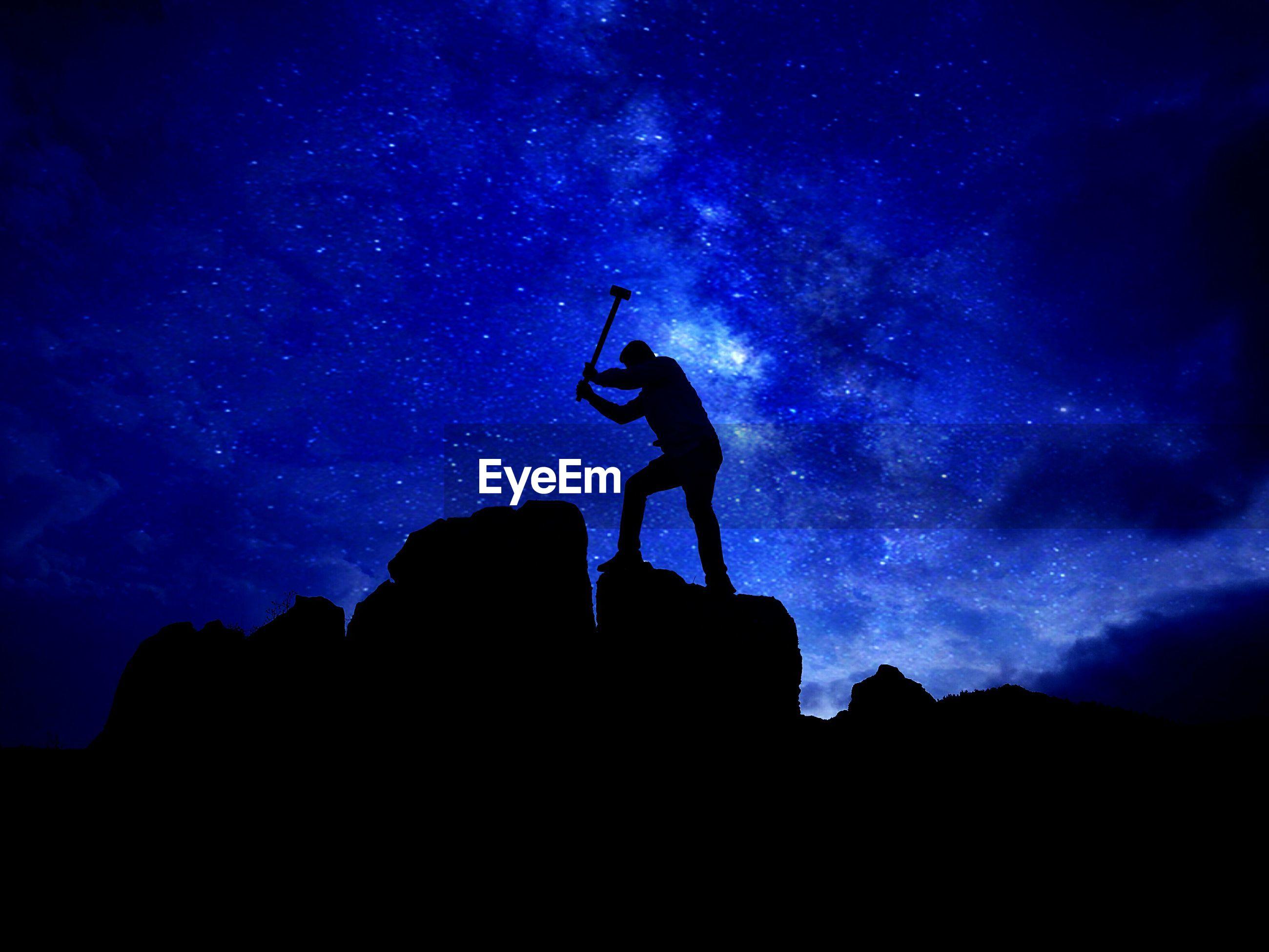 Silhouette man hammering rock against star field at night