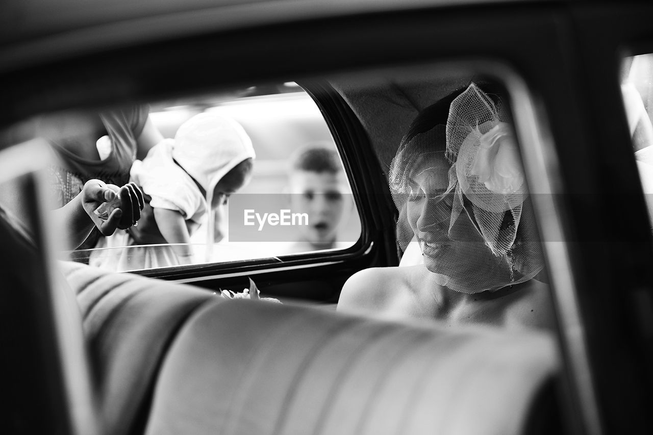 vehicle interior, car, transportation, mode of transport, car interior, land vehicle, real people, travel, public transportation, journey, one person, flower, women, music, day, indoors, vehicle seat, men, close-up, young adult, people