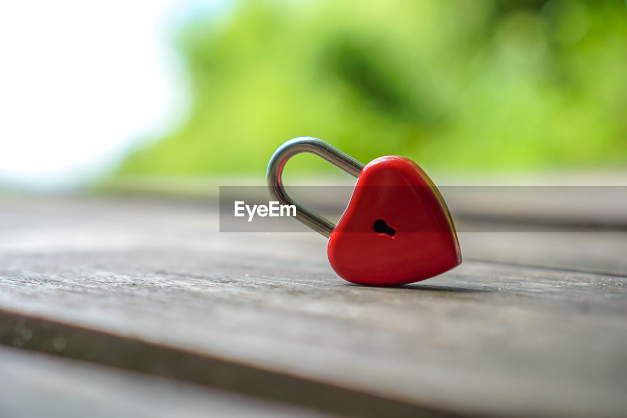 selective focus, red, day, close-up, no people, still life, single object, outdoors, green color, nature, heart shape, wood - material, table, metal, absence, park, railing, focus on foreground, park - man made space, security, personal accessory