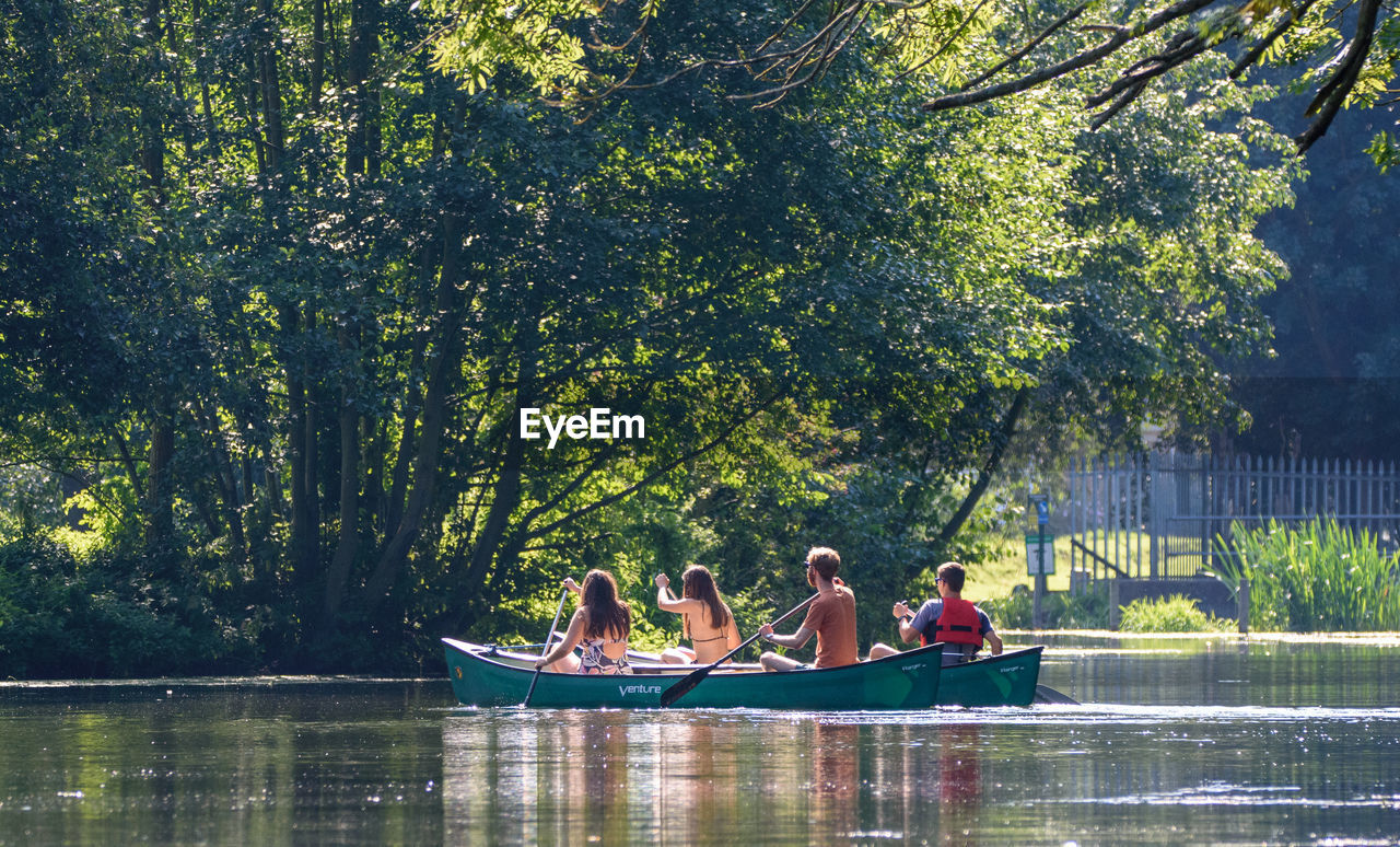 water, group of people, tree, plant, leisure activity, women, togetherness, real people, nature, lifestyles, day, adult, sitting, lake, transportation, people, waterfront, men, outdoors, positive emotion