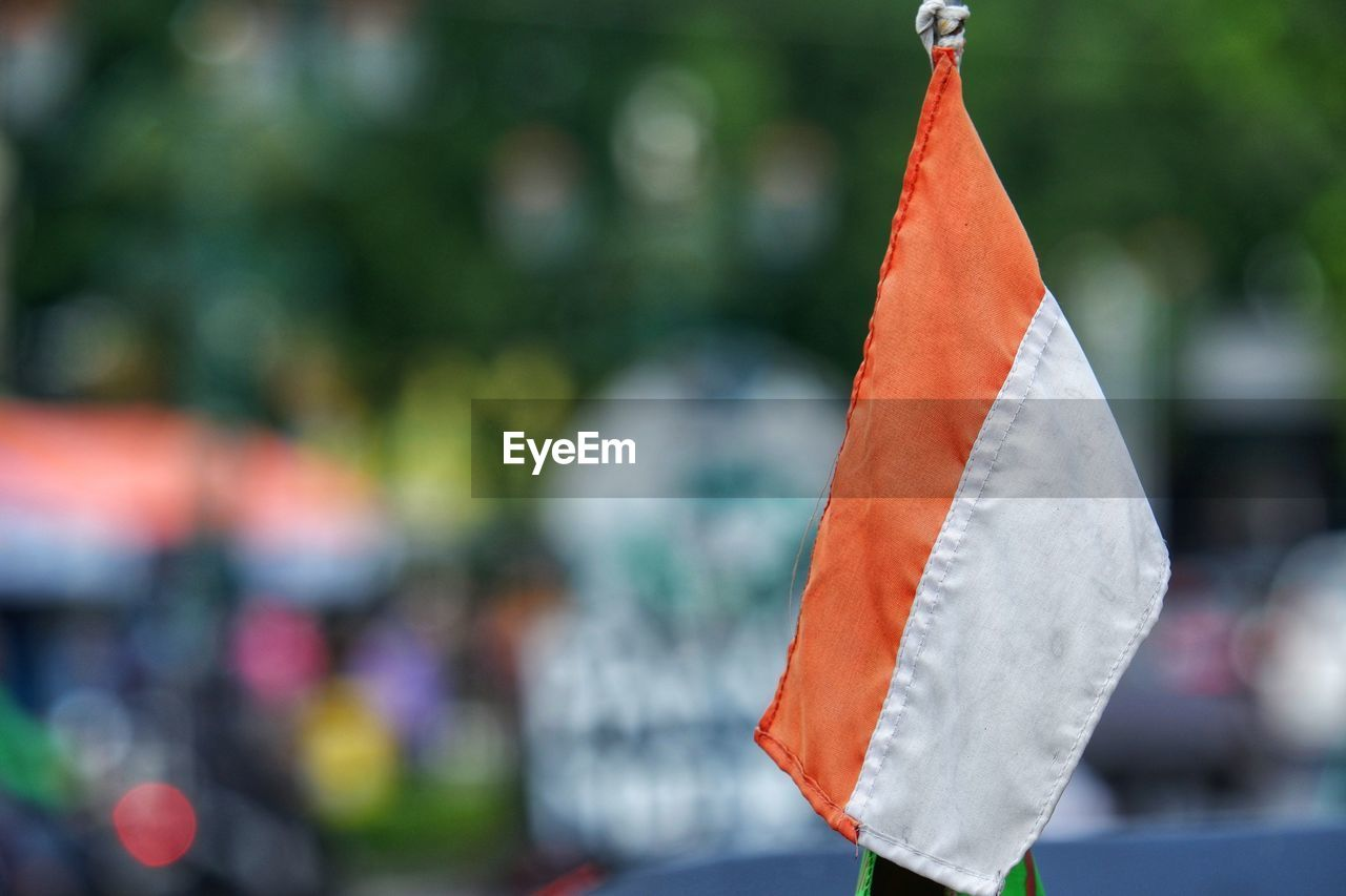 focus on foreground, close-up, day, cone, no people, orange color, outdoors, flag, red, celebration, nature, paper, holiday, food, food and drink, art and craft, textile, hanging, water