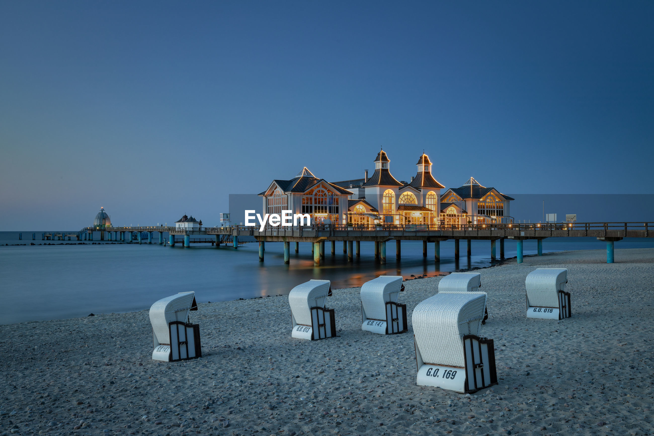 Hooded chairs at beach by stilt houses over sea against clear sky