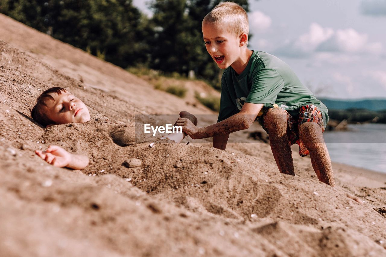 Children Playing On Sand At Beach Against Sky