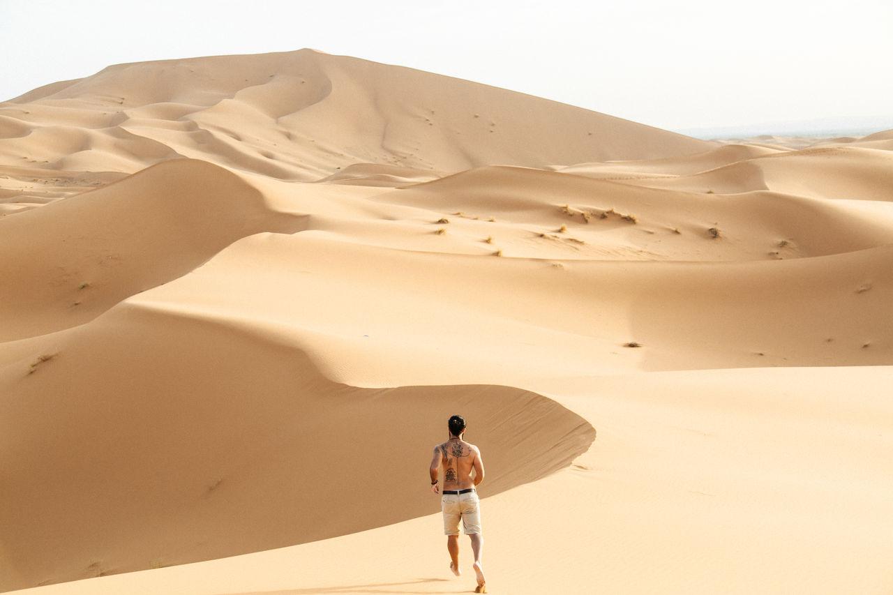 Rear View Of Man Running In Desert