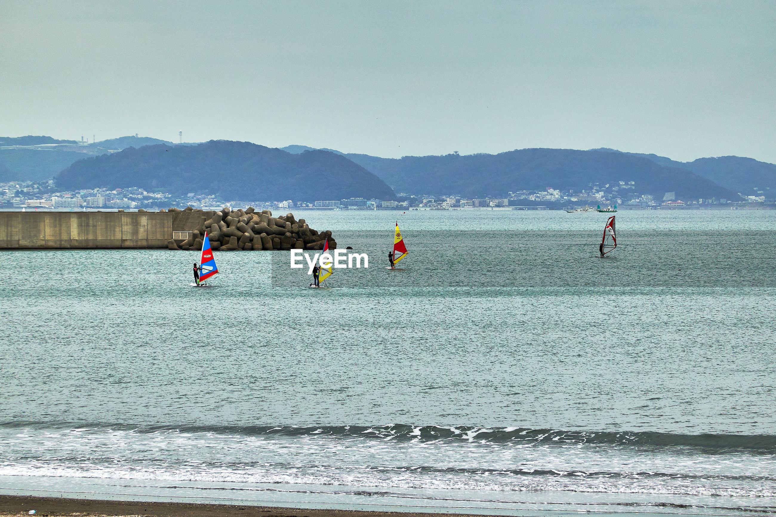 People enjoying marine sports against sky