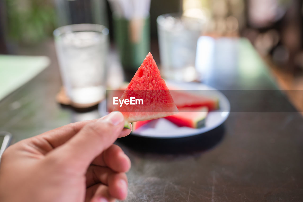 human hand, food and drink, food, one person, human body part, hand, freshness, holding, real people, healthy eating, fruit, table, lifestyles, wellbeing, unrecognizable person, red, selective focus, watermelon, sweet food, body part, finger, temptation