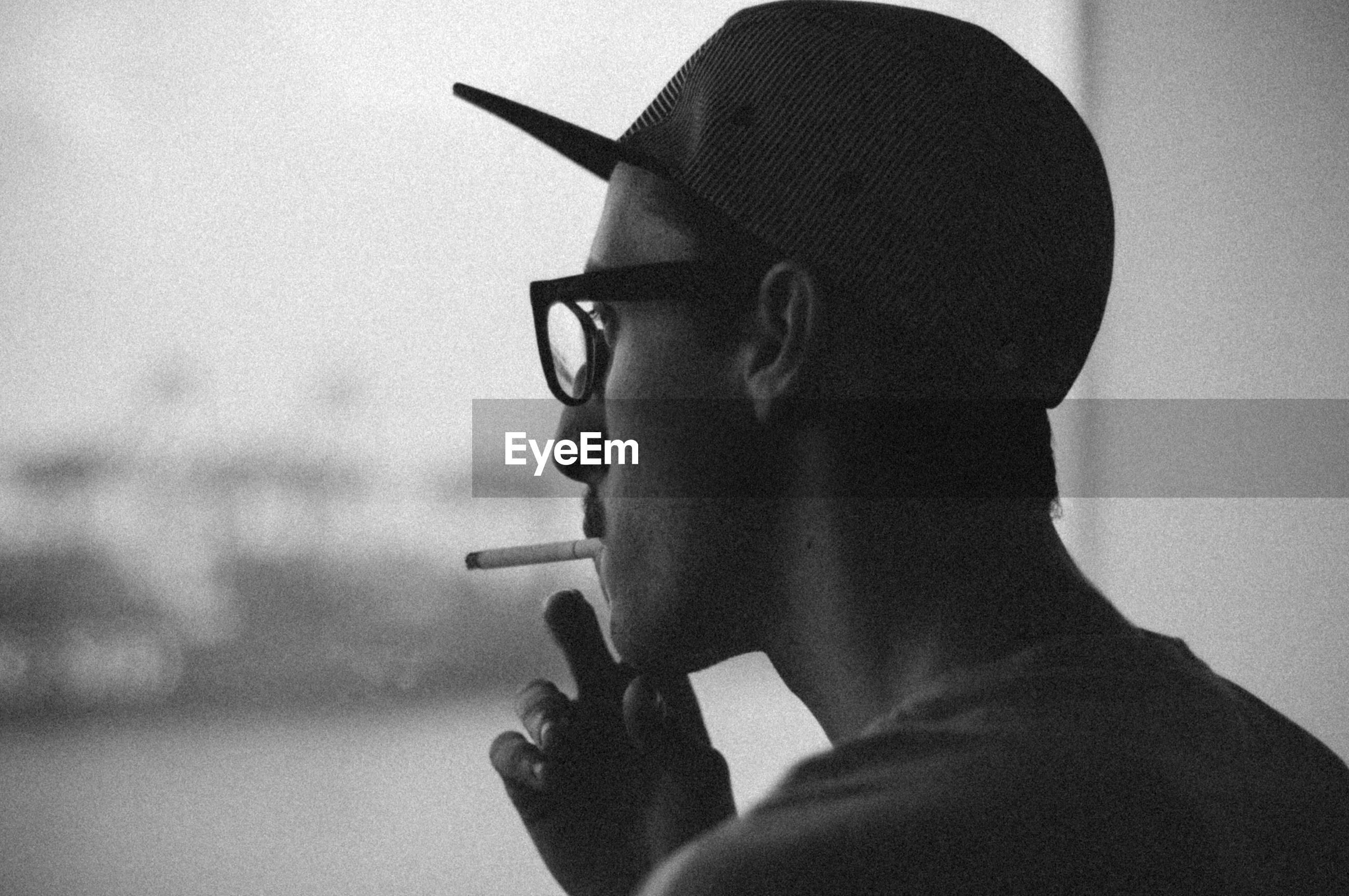 Side view of man smoking a cigarette