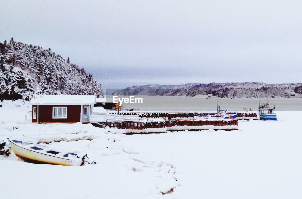 Boats Moored On Frozen River Against Clear Sky