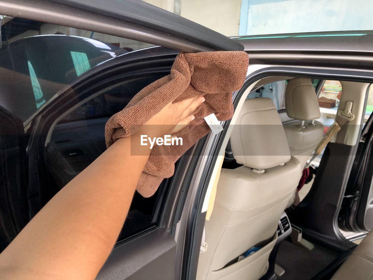 human hand, car, real people, mode of transportation, hand, human body part, motor vehicle, transportation, land vehicle, lifestyles, one person, holding, vehicle interior, cleaning, glass - material, women, day, unrecognizable person, adult, finger