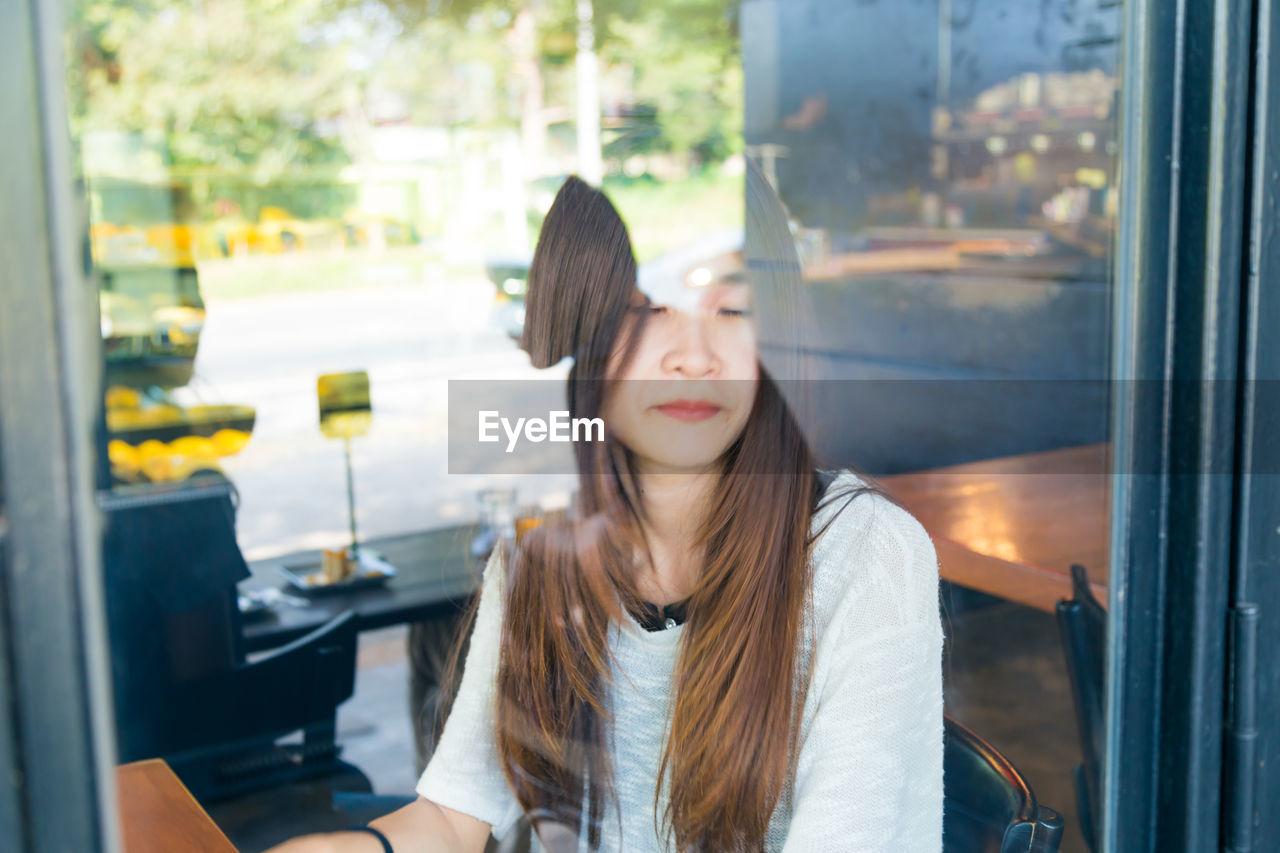 Woman sitting in restaurant seen through window