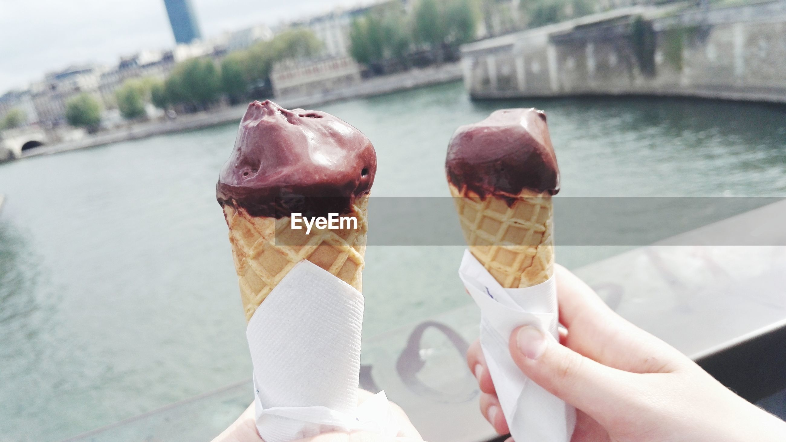 Cropped hand of woman holding ice cream cones against river