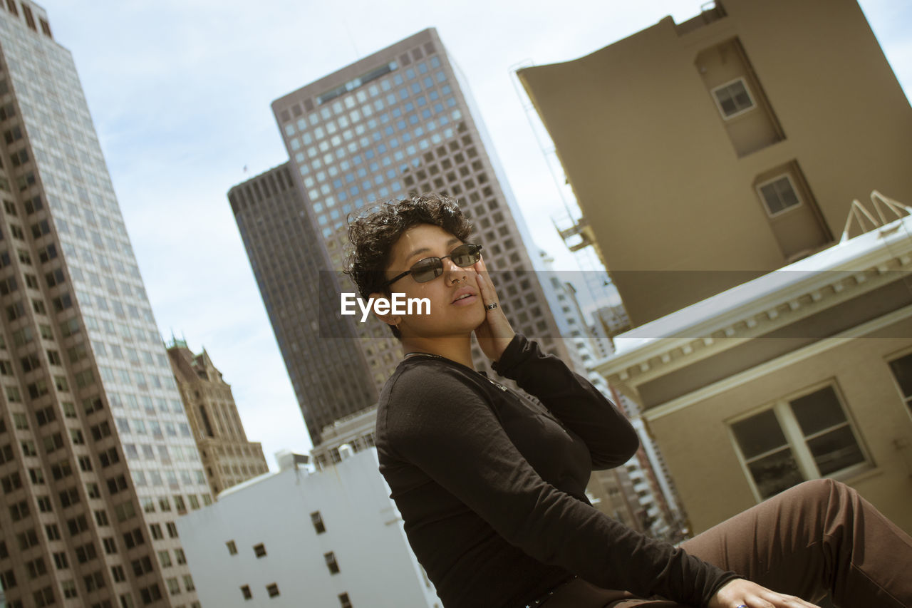 LOW ANGLE VIEW OF YOUNG WOMAN LOOKING AT BUILDINGS