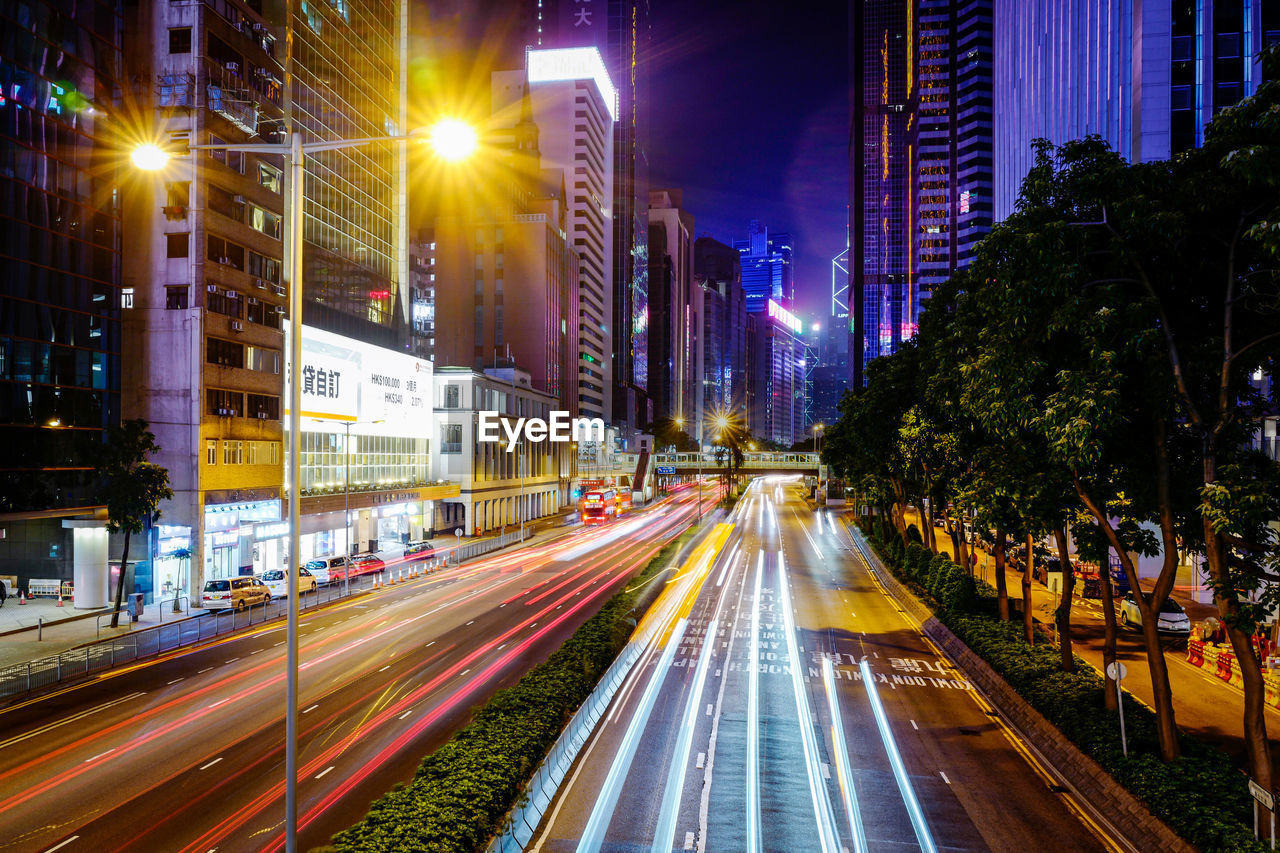 illuminated, city, night, building exterior, architecture, street, built structure, motion, long exposure, speed, city life, city street, light trail, road, street light, transportation, blurred motion, building, mode of transportation, traffic, office building exterior, light
