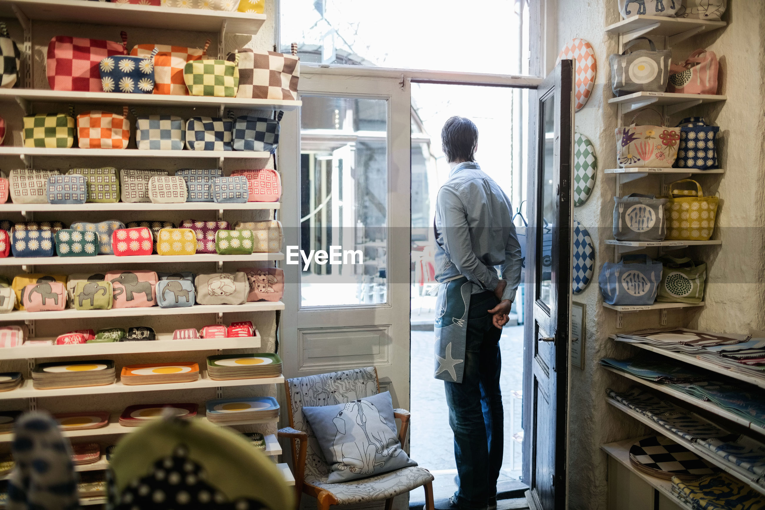 REAR VIEW OF MAN STANDING AT STORE
