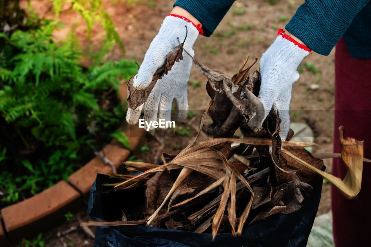 Midsection of person wearing gloves working at backyard
