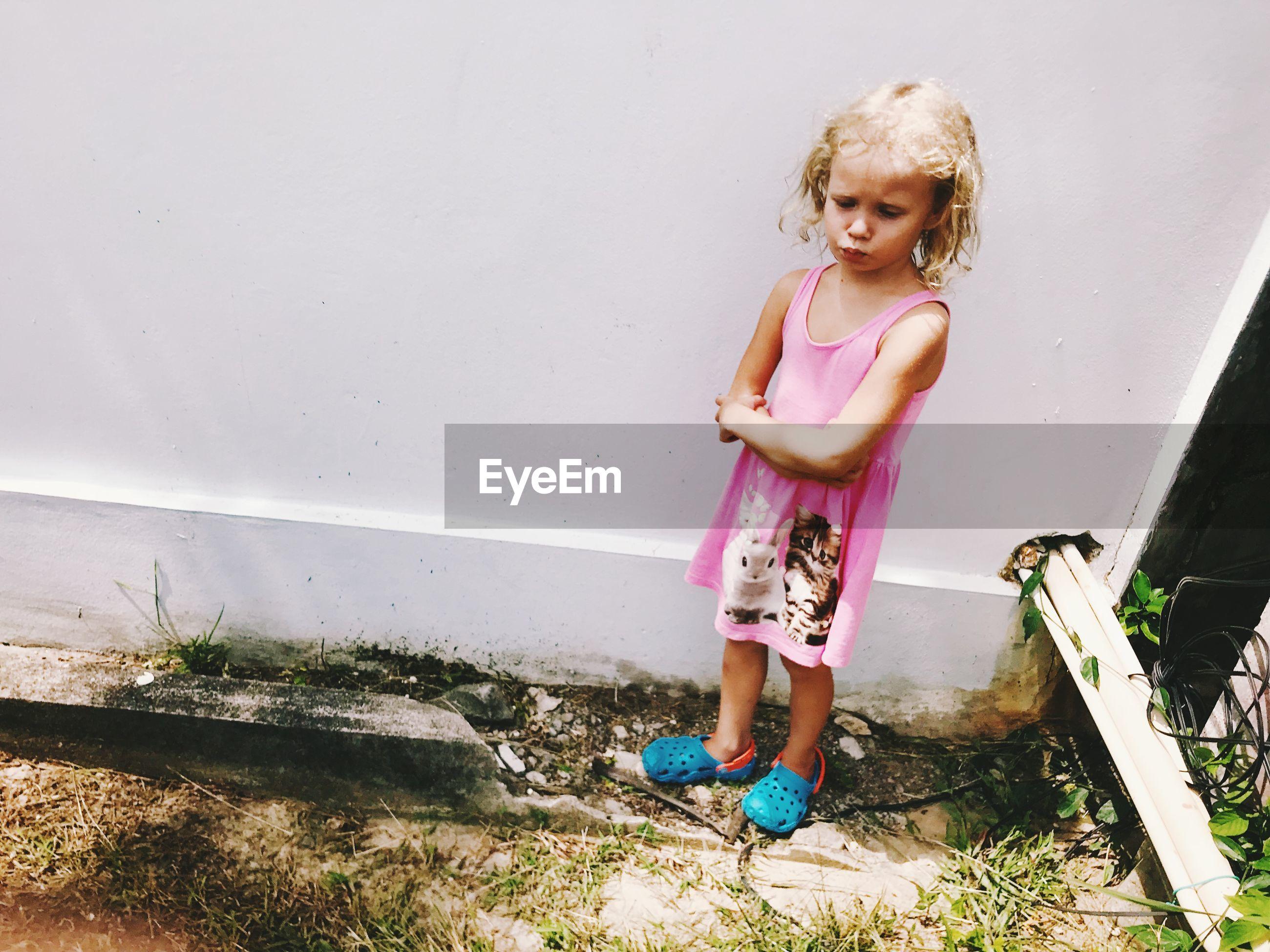 Full length of sad girl standing against wall