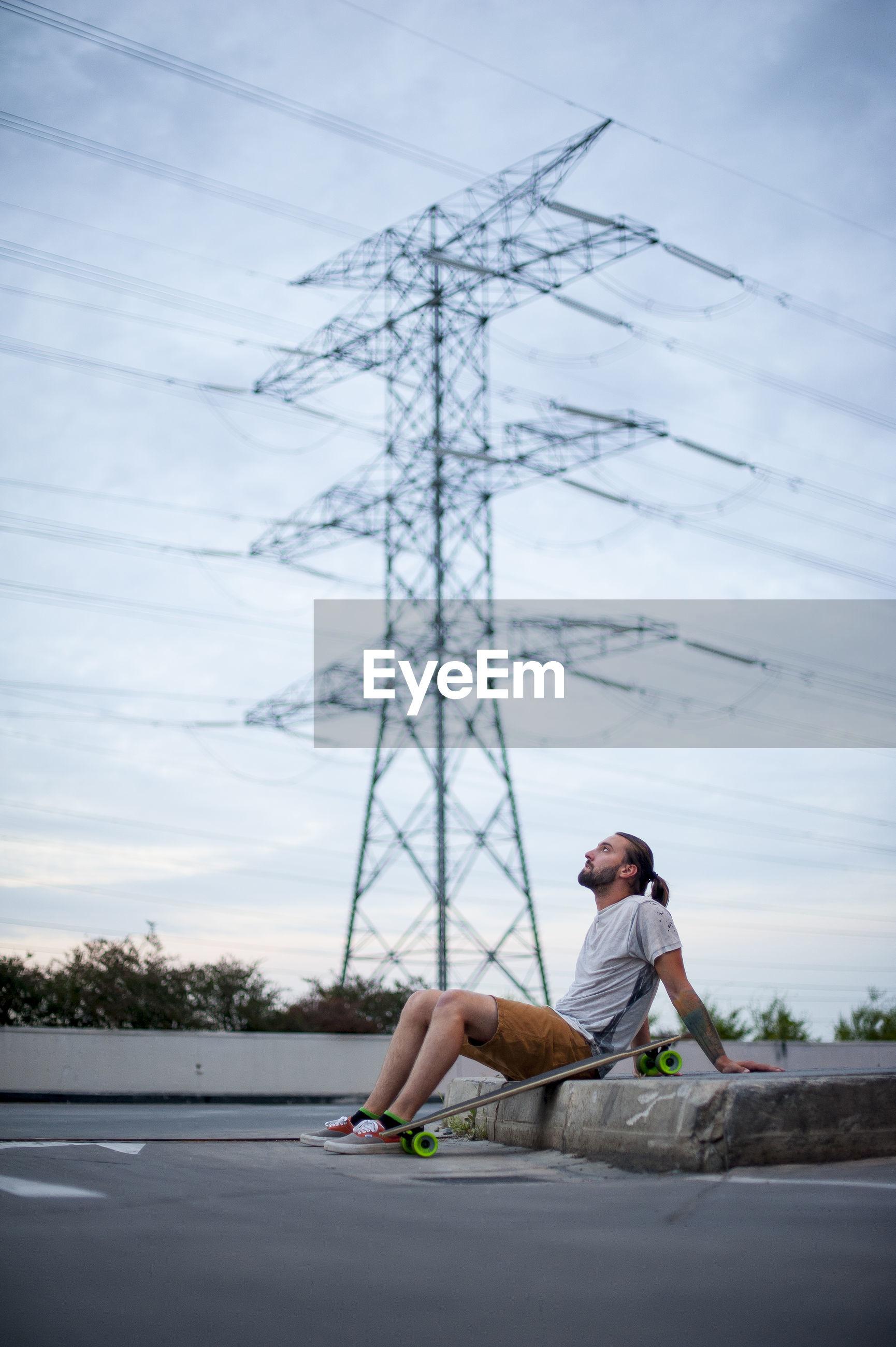 FULL LENGTH OF MAN SITTING ON MOBILE PHONE AGAINST SKY