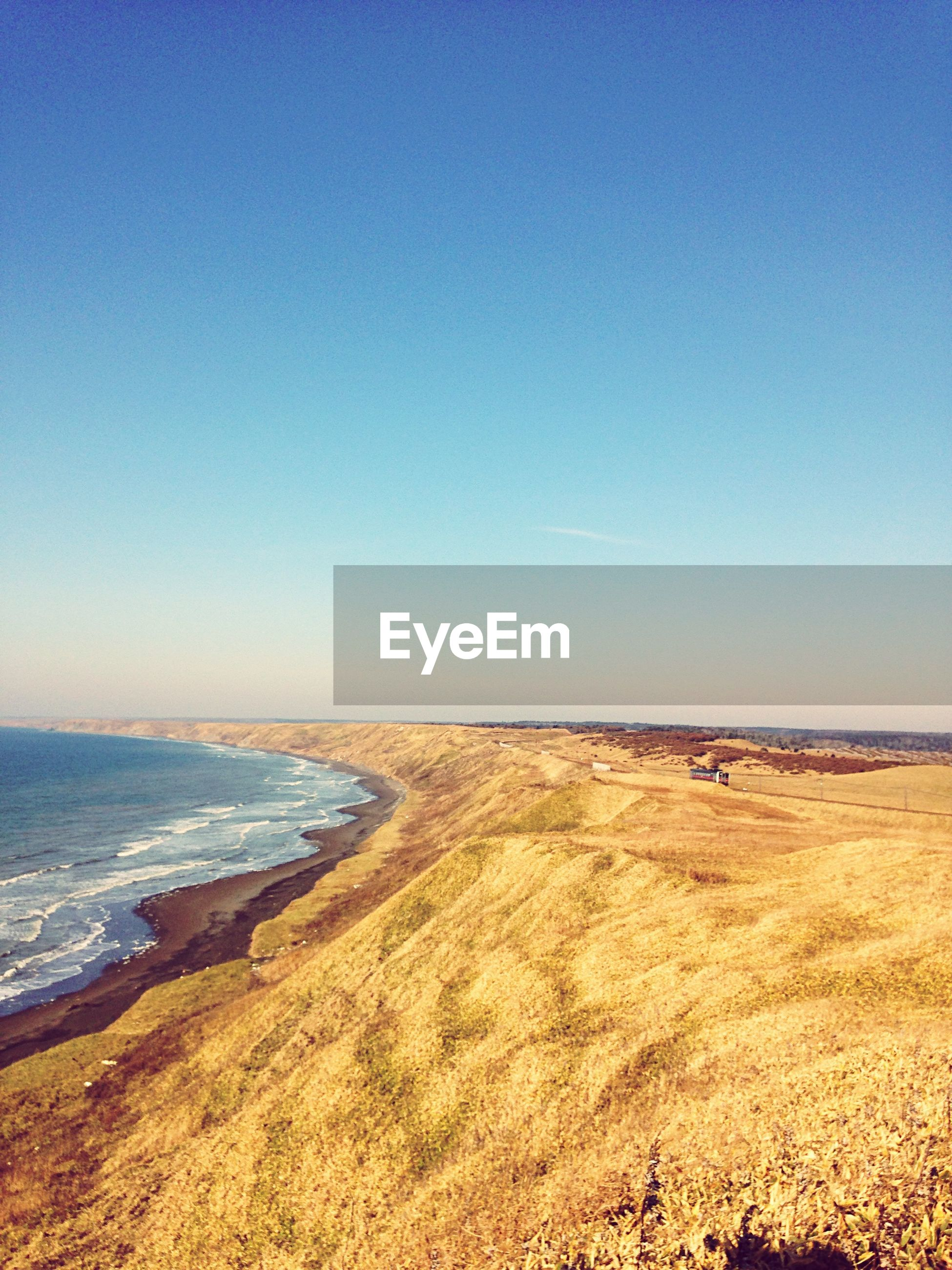 sea, beach, clear sky, tranquil scene, sand, copy space, tranquility, water, scenics, horizon over water, shore, beauty in nature, blue, nature, coastline, idyllic, remote, non-urban scene, day, outdoors