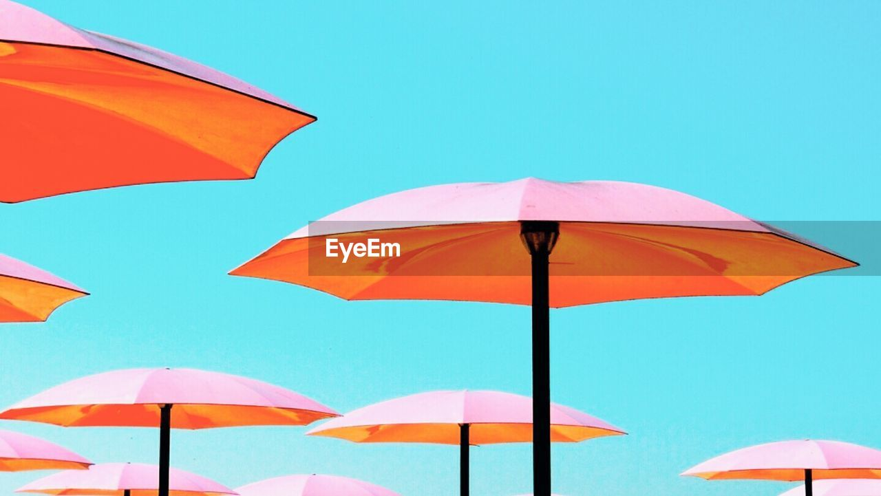 protection, umbrella, security, sky, blue, nature, clear sky, parasol, low angle view, safety, day, multi colored, no people, outdoors, shade, beach umbrella, sunlight, copy space, red