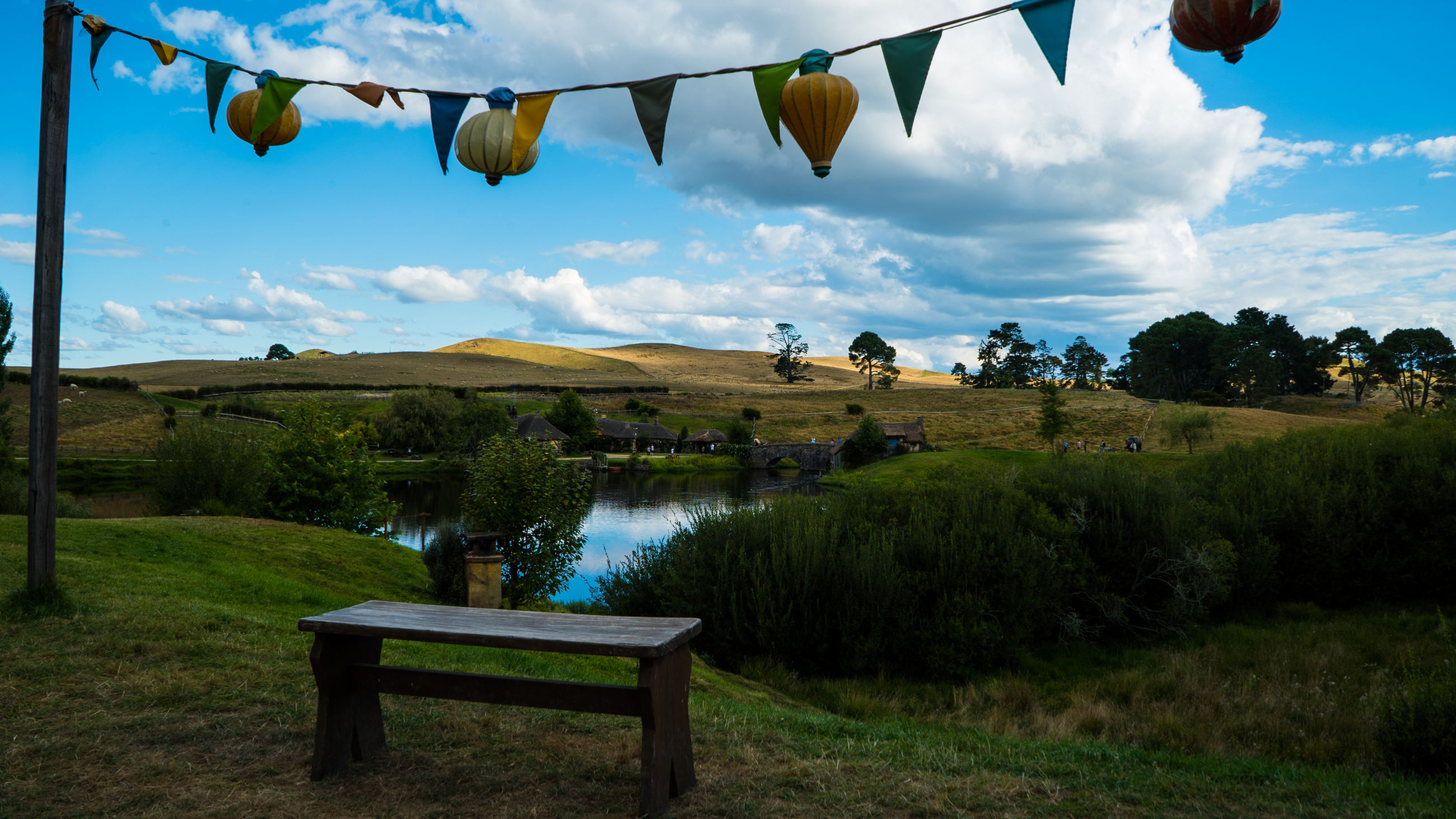 Bunting hanging over empty seat by lake against sky