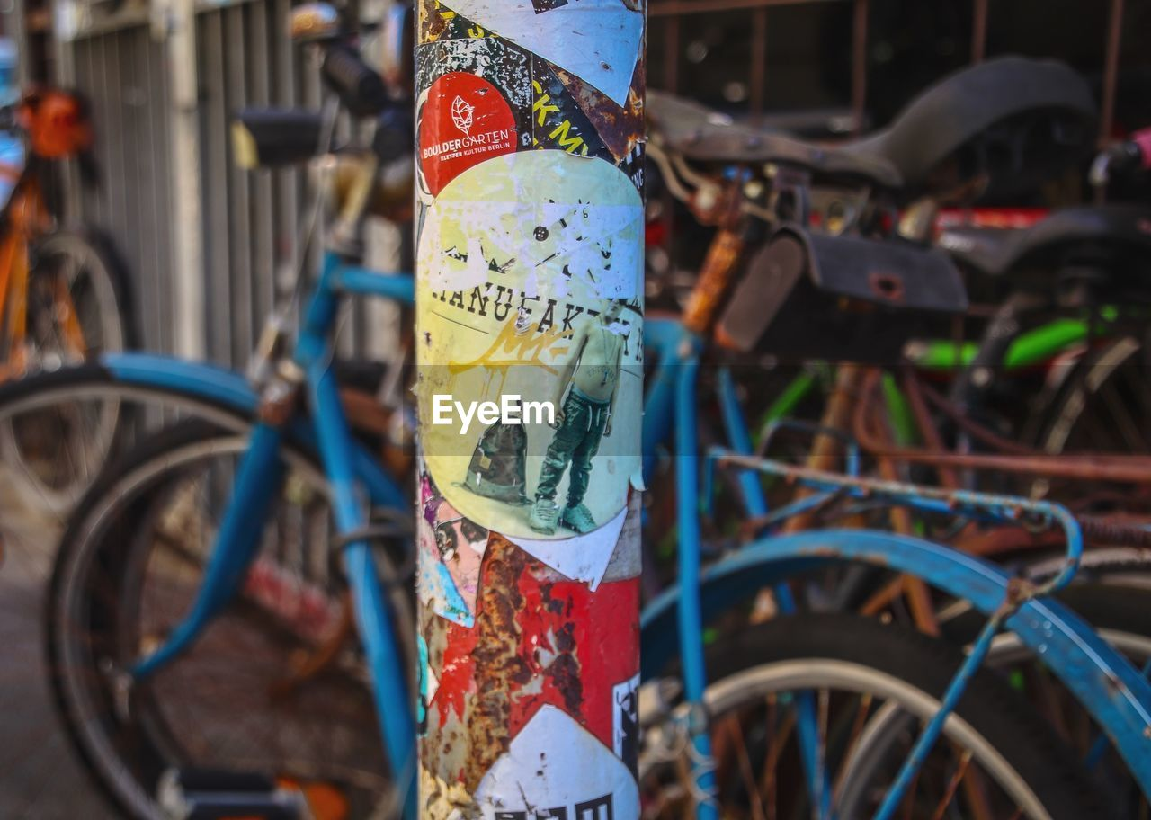 bicycle, transportation, land vehicle, mode of transportation, selective focus, stationary, no people, close-up, focus on foreground, day, text, multi colored, communication, outdoors, metal, blue, city, parking, travel, western script