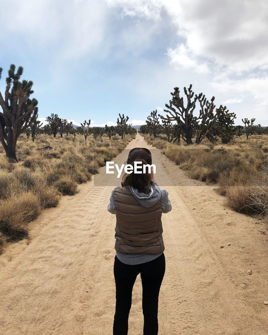 Rear view of woman standing at dirt road against sky