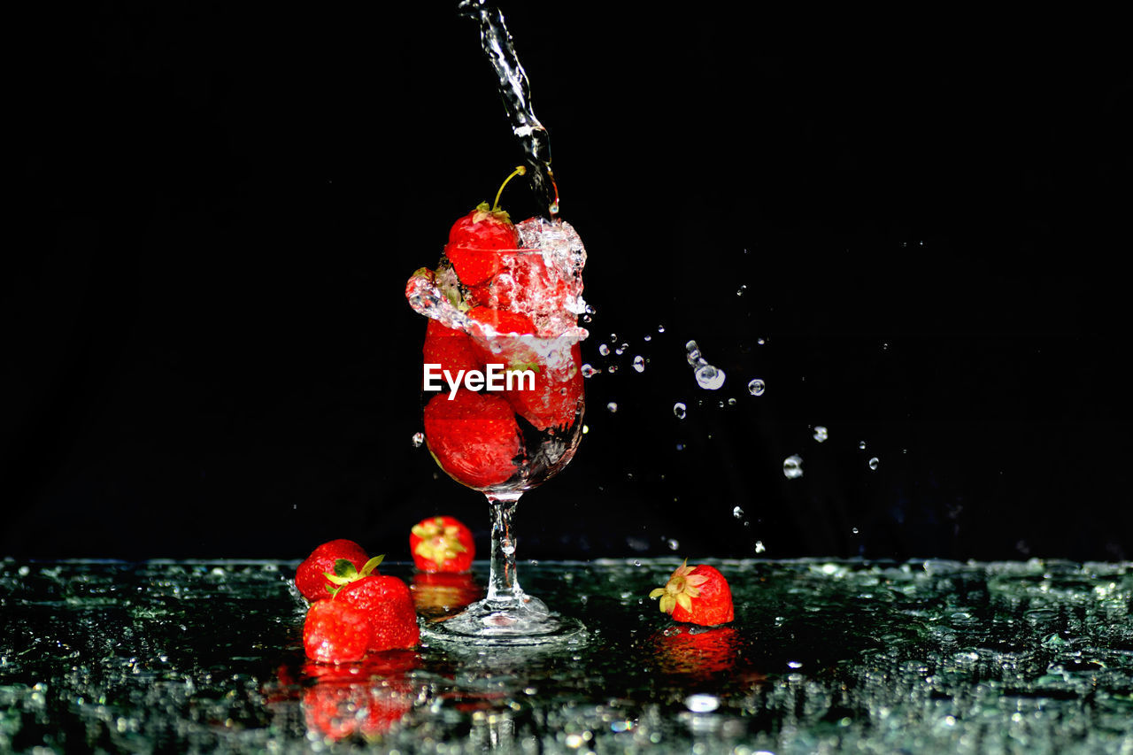 water, red, black background, splashing, studio shot, no people, freshness, fruit, food and drink, indoors, motion, close-up, nature, healthy eating, food, drop, berry fruit, glass, high-speed photography