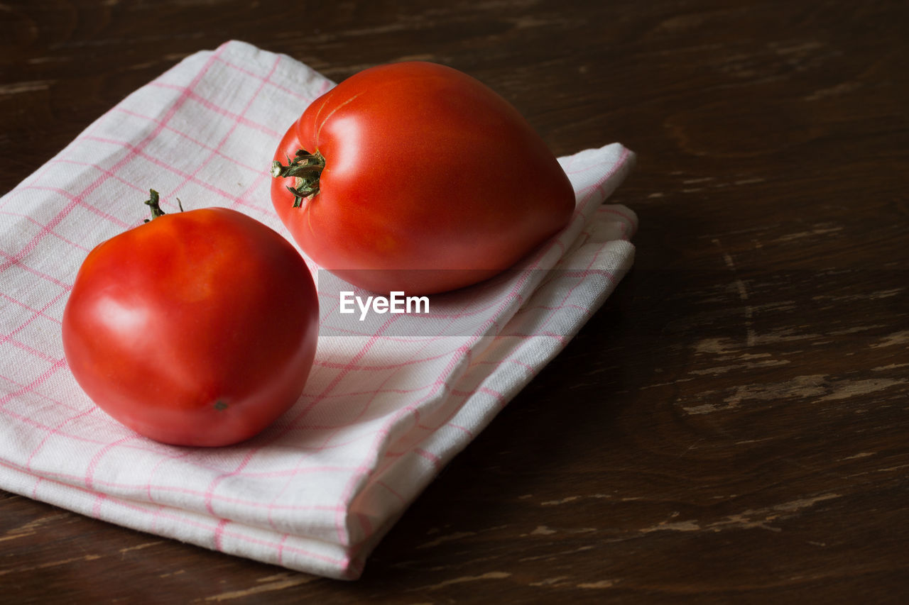 table, food, food and drink, wellbeing, still life, healthy eating, red, freshness, fruit, indoors, tomato, wood - material, close-up, high angle view, no people, vegetable, cutting board, focus on foreground, raw food, napkin, ripe