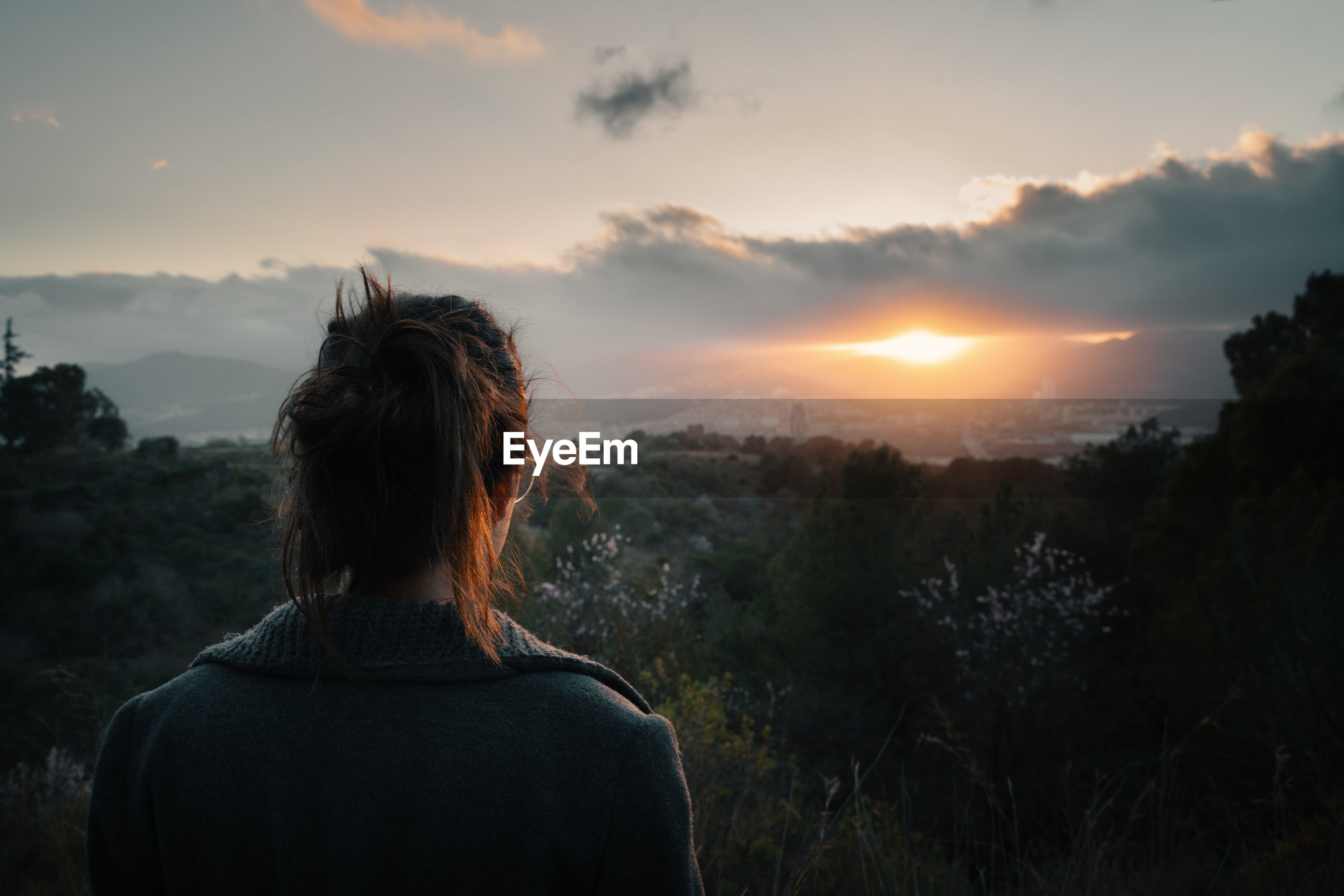 REAR VIEW OF WOMAN LOOKING AT SUNSET OVER MOUNTAIN