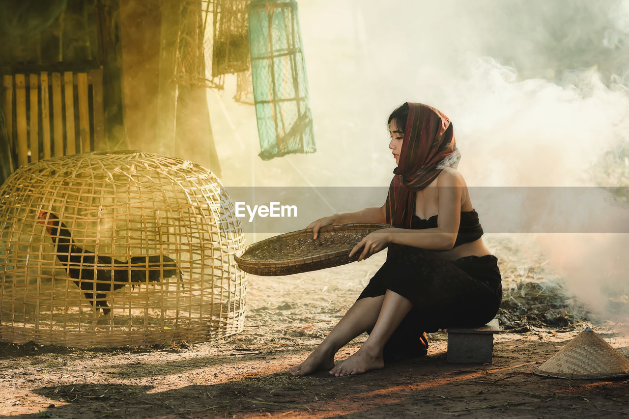 Woman Holding Wicker Container While Sitting On Field