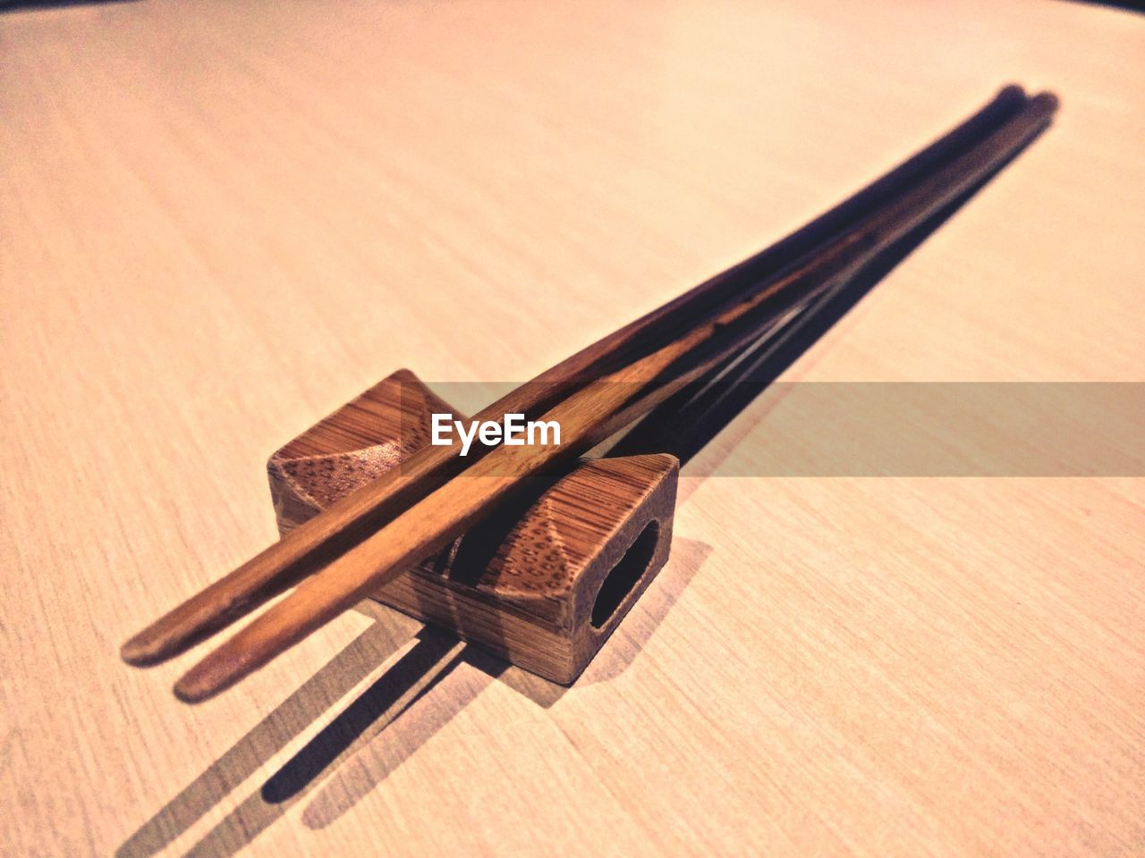 wood - material, indoors, still life, no people, table, close-up, high angle view, brown, chopsticks, kitchen utensil, focus on foreground, eating utensil, writing instrument, wood, metal, spoon, shadow, pattern, equipment, pencil, temptation
