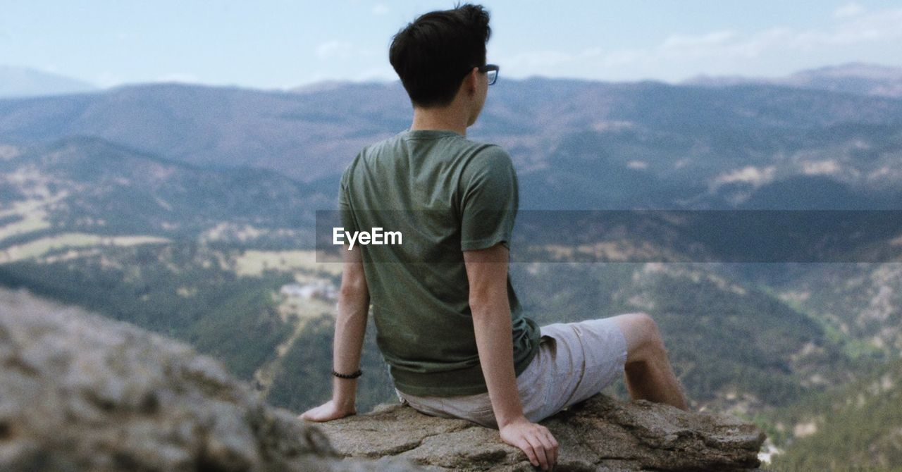 FULL LENGTH OF YOUNG MAN LOOKING AT MOUNTAIN LANDSCAPE