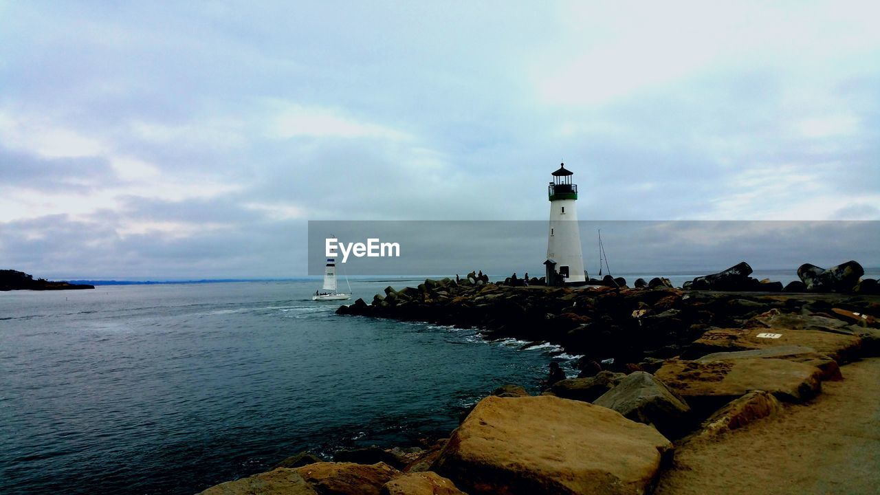 lighthouse, guidance, sea, direction, safety, sky, water, security, protection, nature, rock - object, architecture, horizon over water, built structure, cloud - sky, scenics, tranquility, building exterior, day, beauty in nature, outdoors, no people