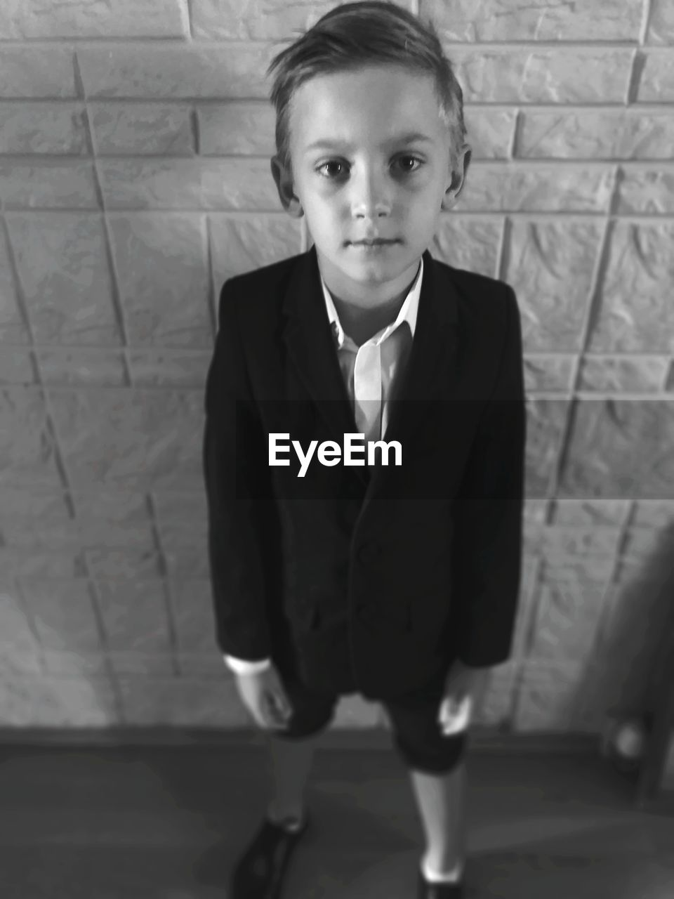 Portrait of boy standing on floor against wall
