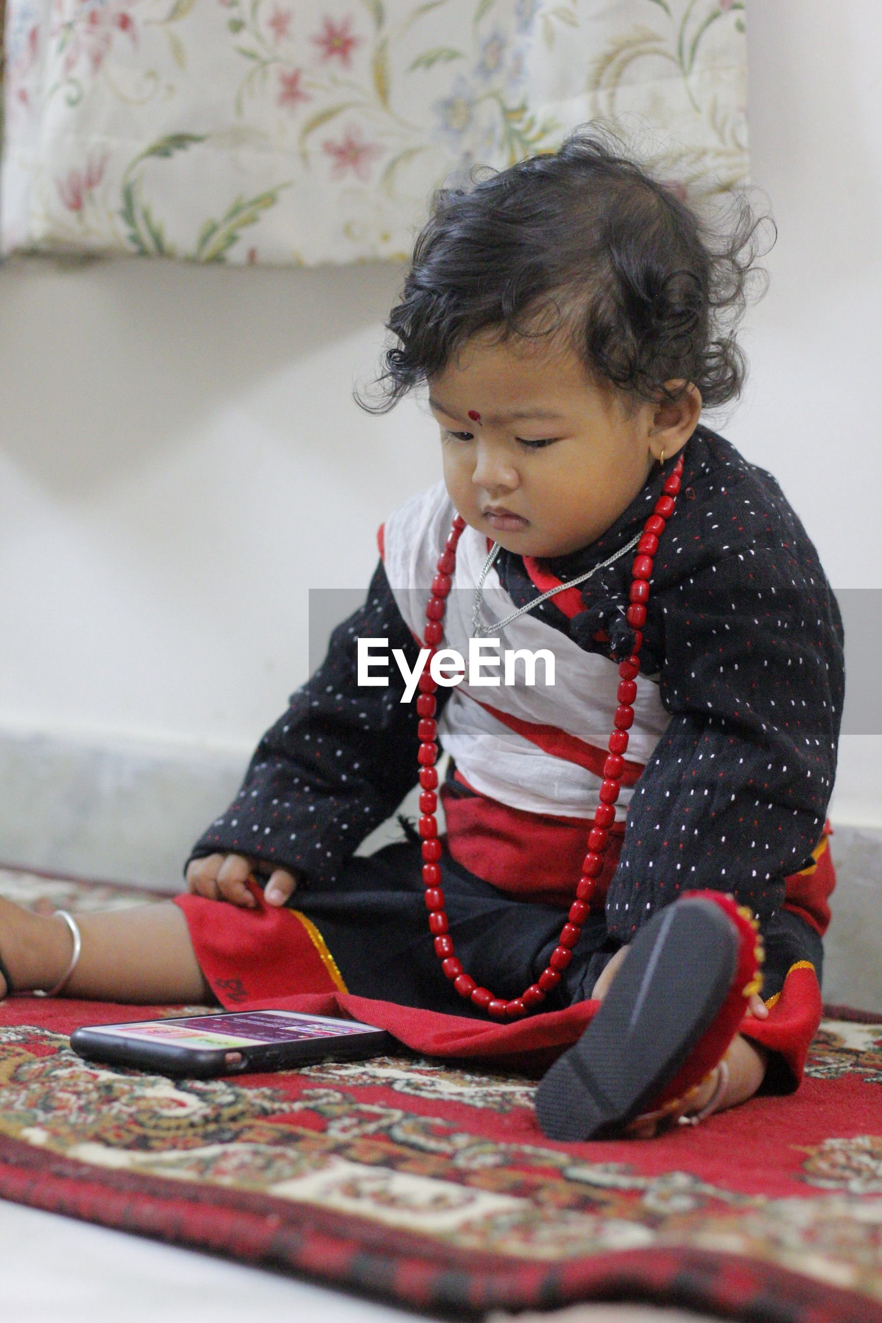 Cute girl sitting and watching mobile phone at home