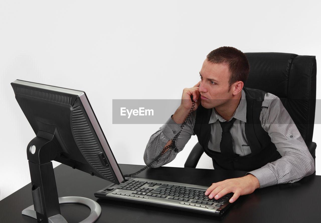 Businessman talking on telephone against white background
