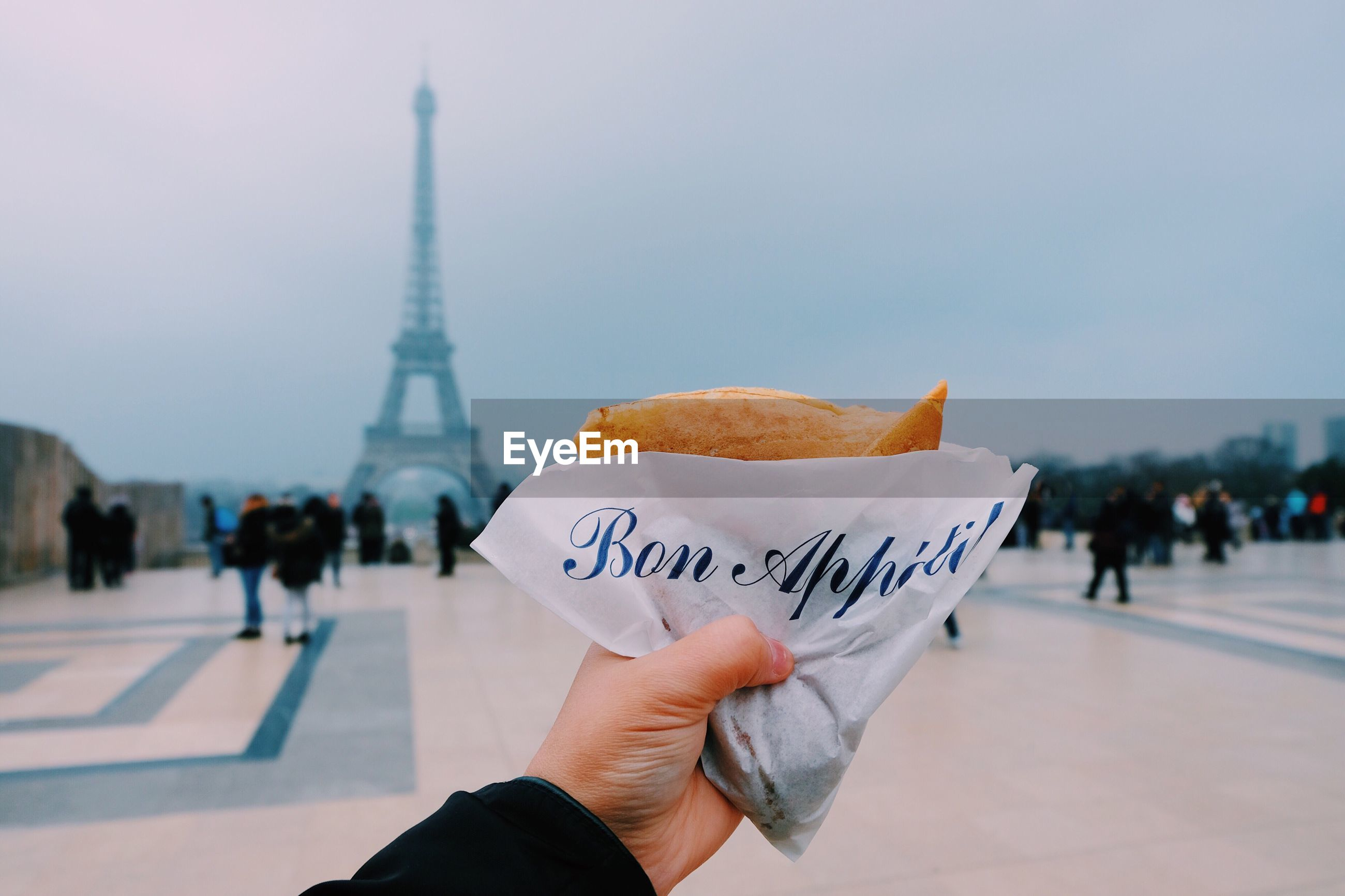 Close-up of hand holding crepe against eiffel tower