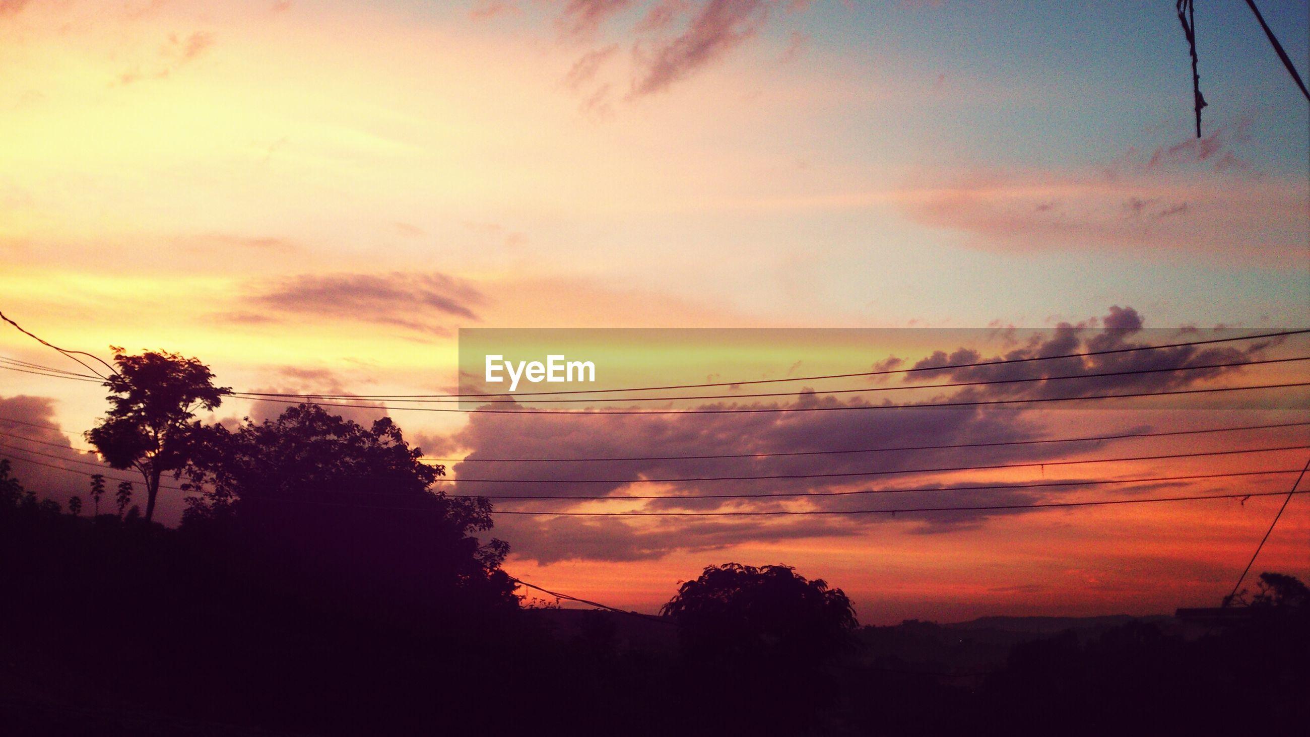 sunset, silhouette, sky, tree, scenics, beauty in nature, tranquil scene, tranquility, orange color, power line, cloud - sky, nature, electricity pylon, idyllic, cloud, dramatic sky, landscape, electricity, dusk, outdoors