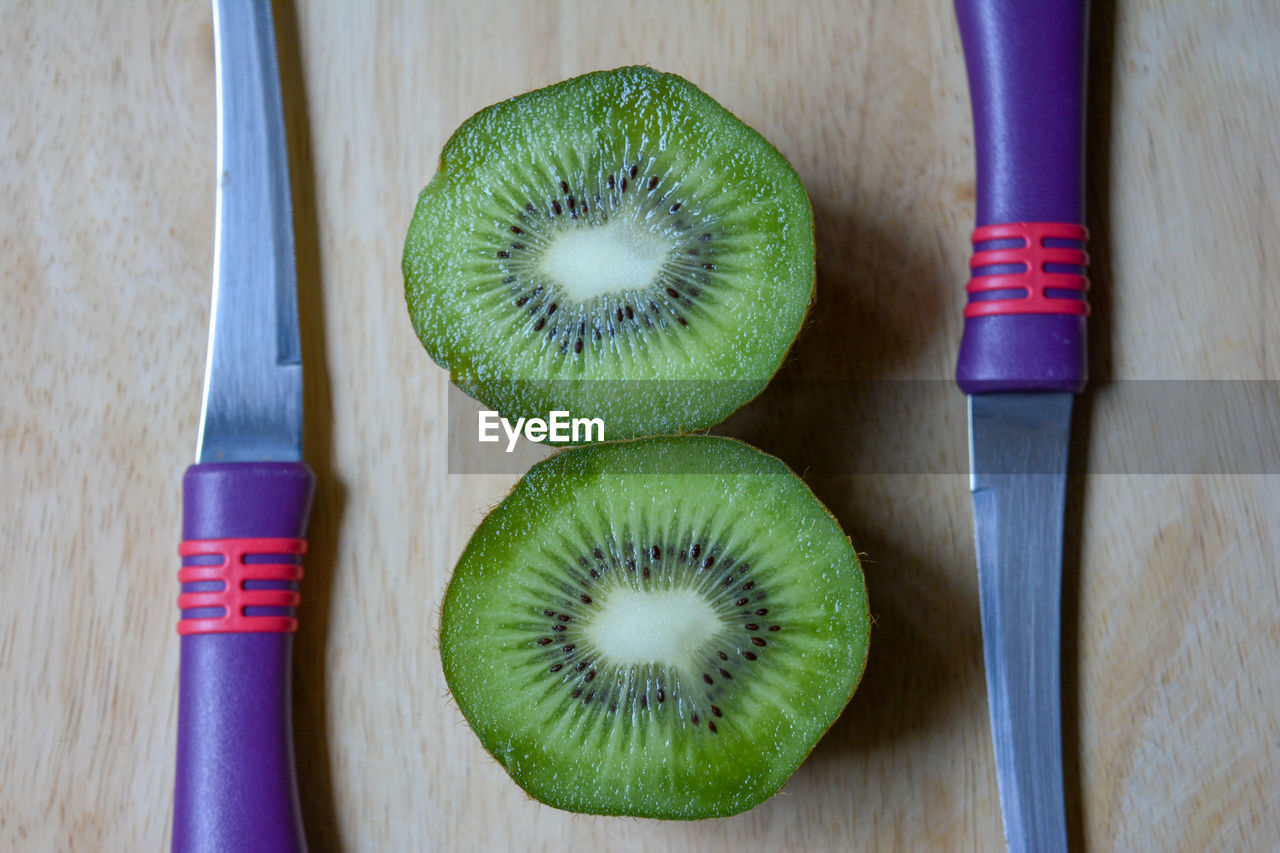 Directly above kiwi slices by knives on table