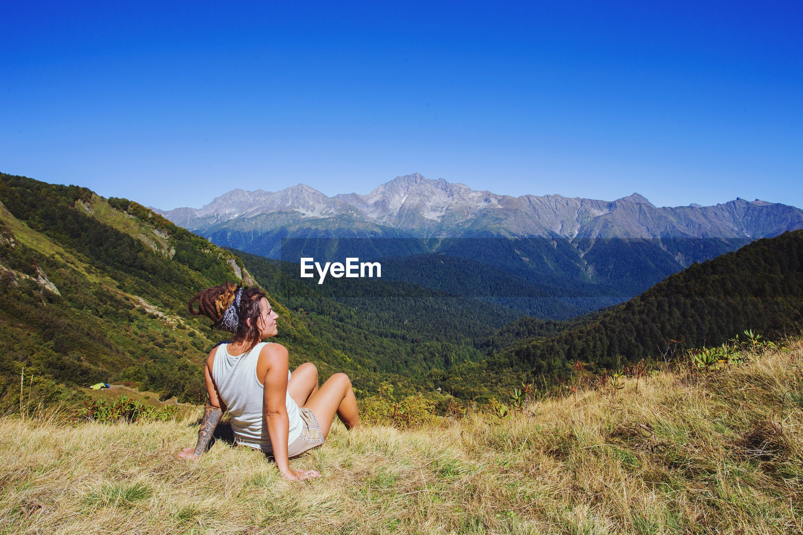 Rear view of woman sitting on mountain against clear blue sky
