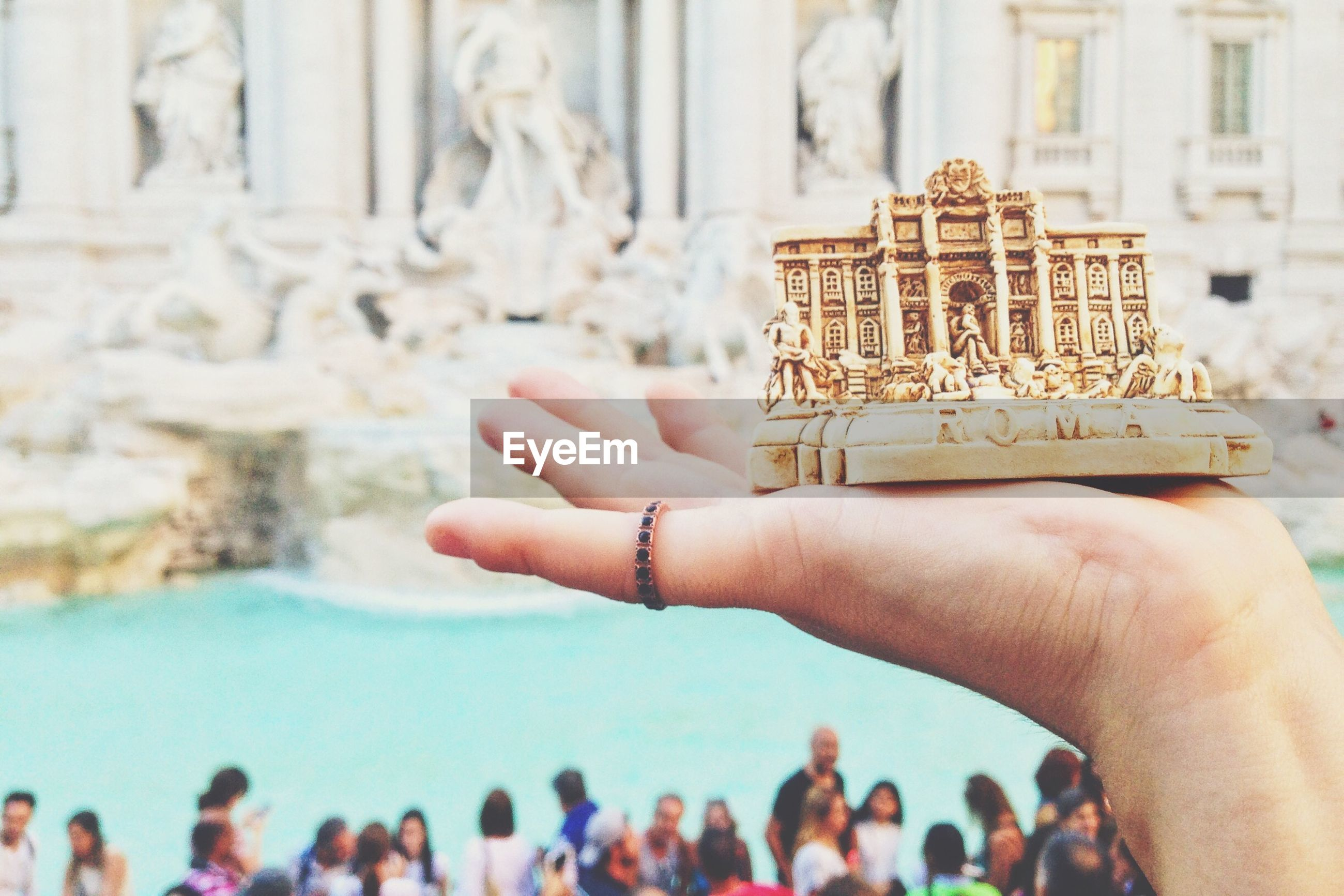 Close-up of person hands holding piazza di trevi statue